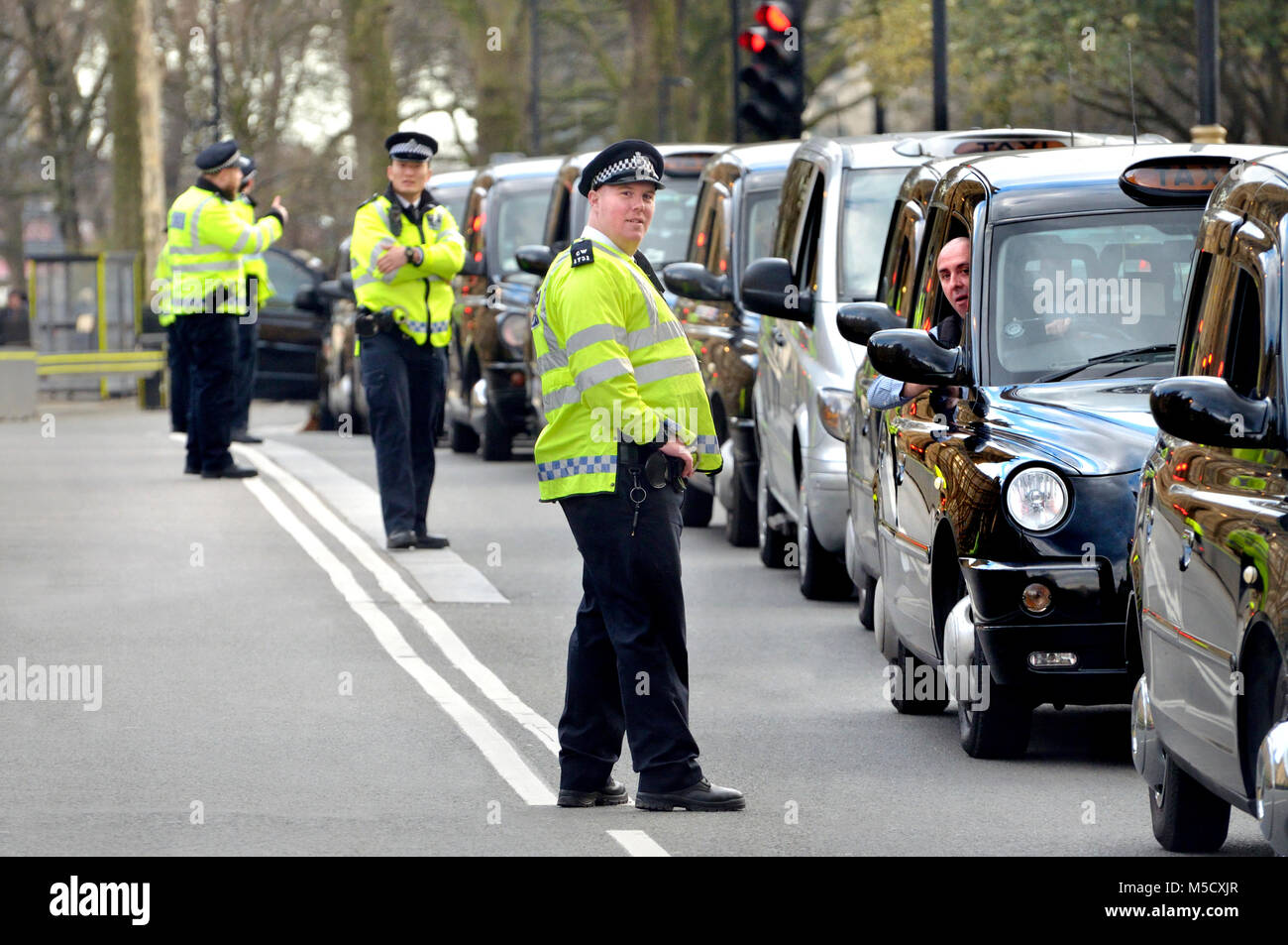 London, England, UK. Police and taxi drivers during a protest against the Uber taxi app - Stock Image