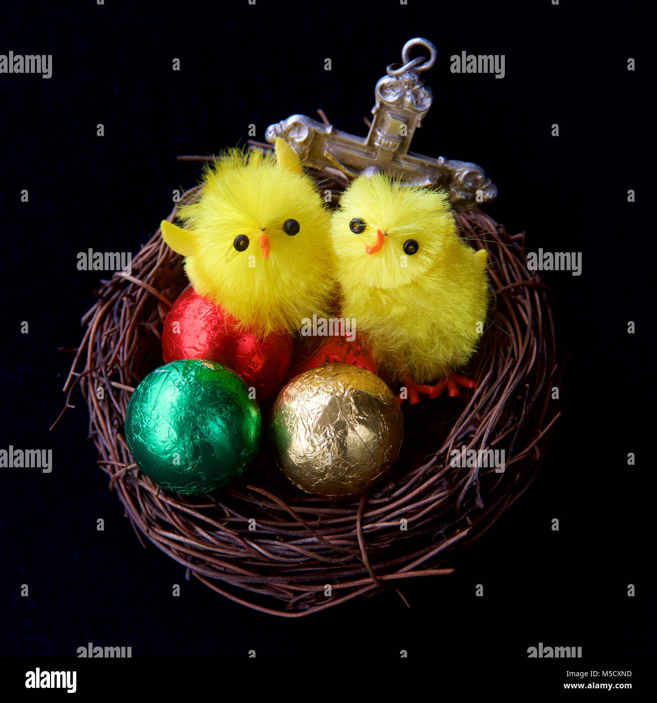 Two young chickens in a nest with eggs and a cross at Easter. - Stock Image