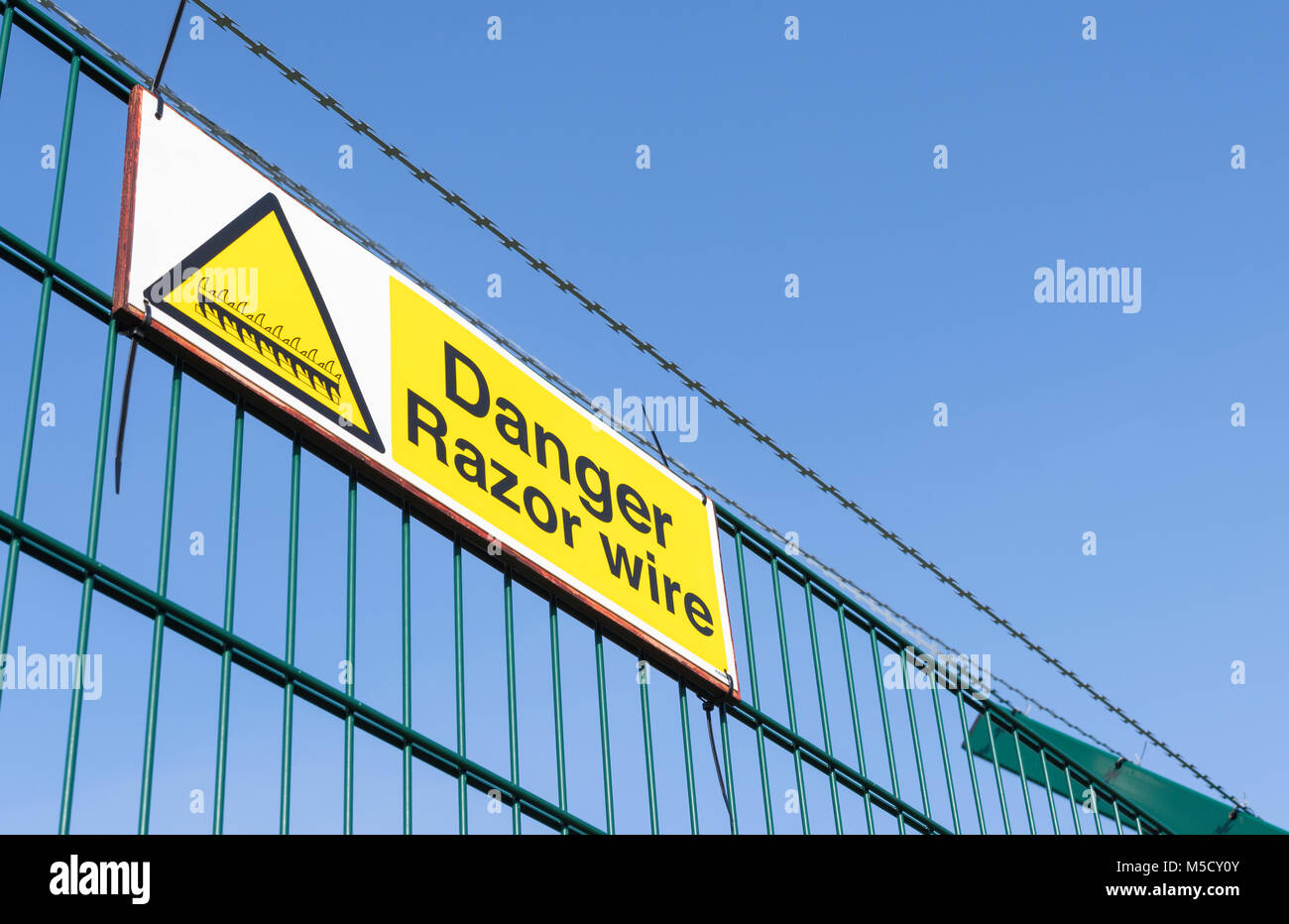 Danger Razor Wire warning sign on top of a security fence in the UK. - Stock Image