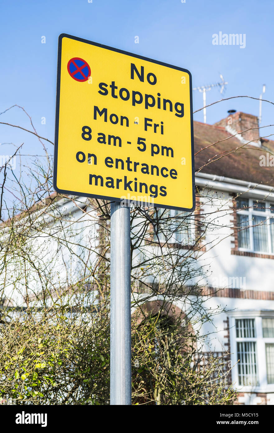 Yellow no stopping warning sign on a roadside in England, UK. - Stock Image