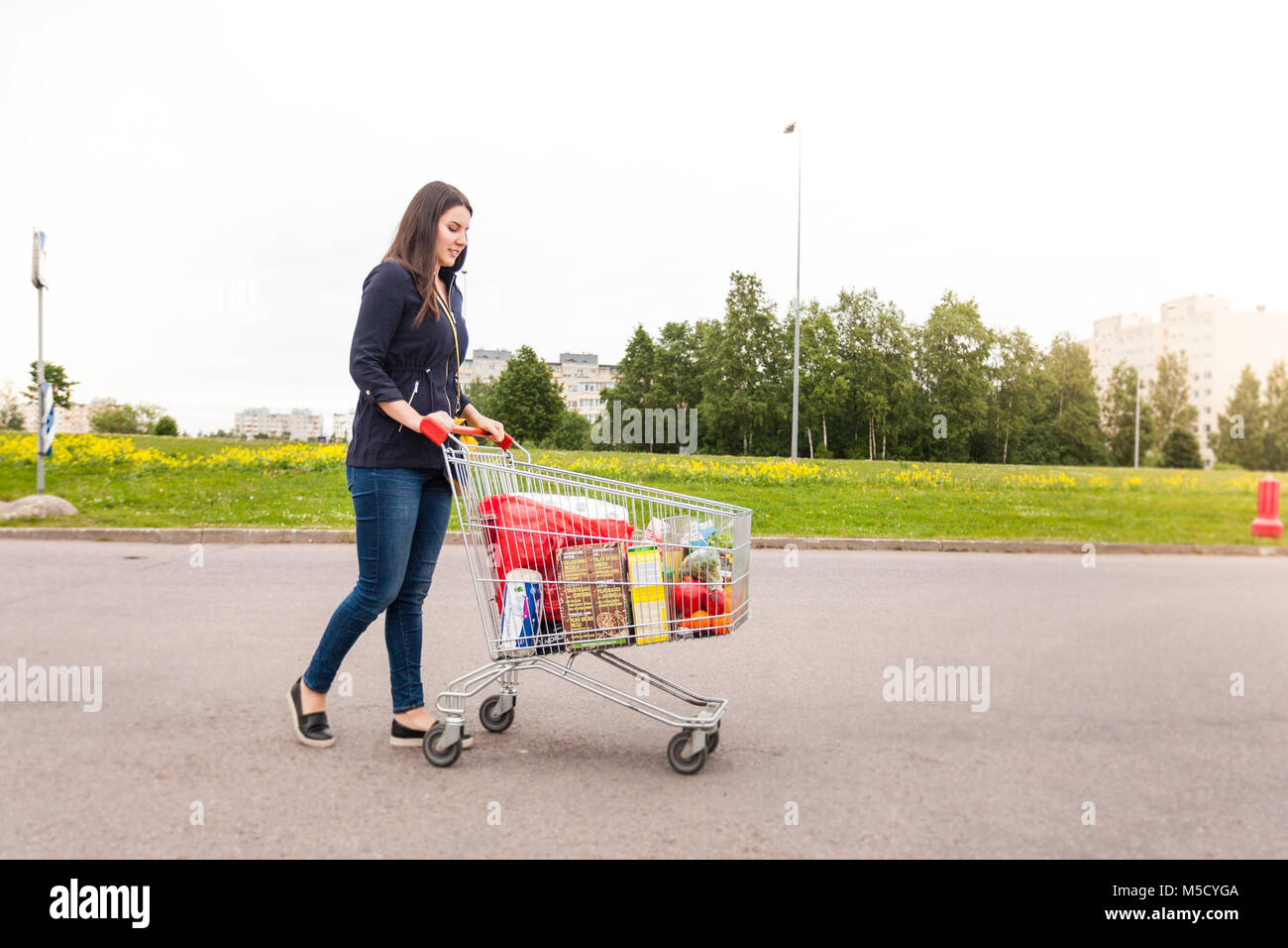 Cute smiling teen looks into a camera with food products she bought - Stock Image