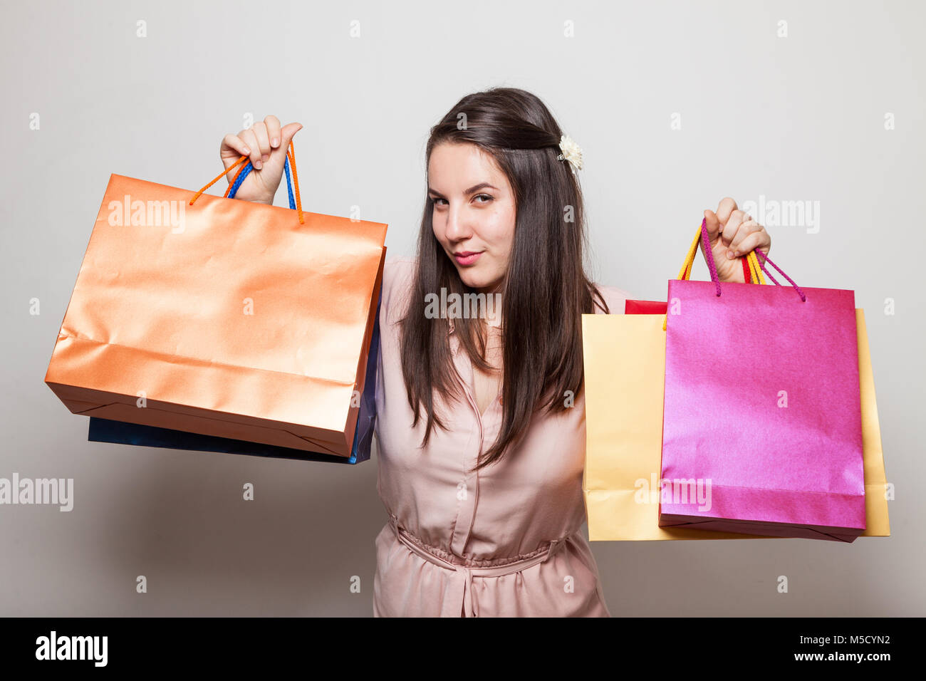 Girl has a tricky glance holding gift bags - Stock Image