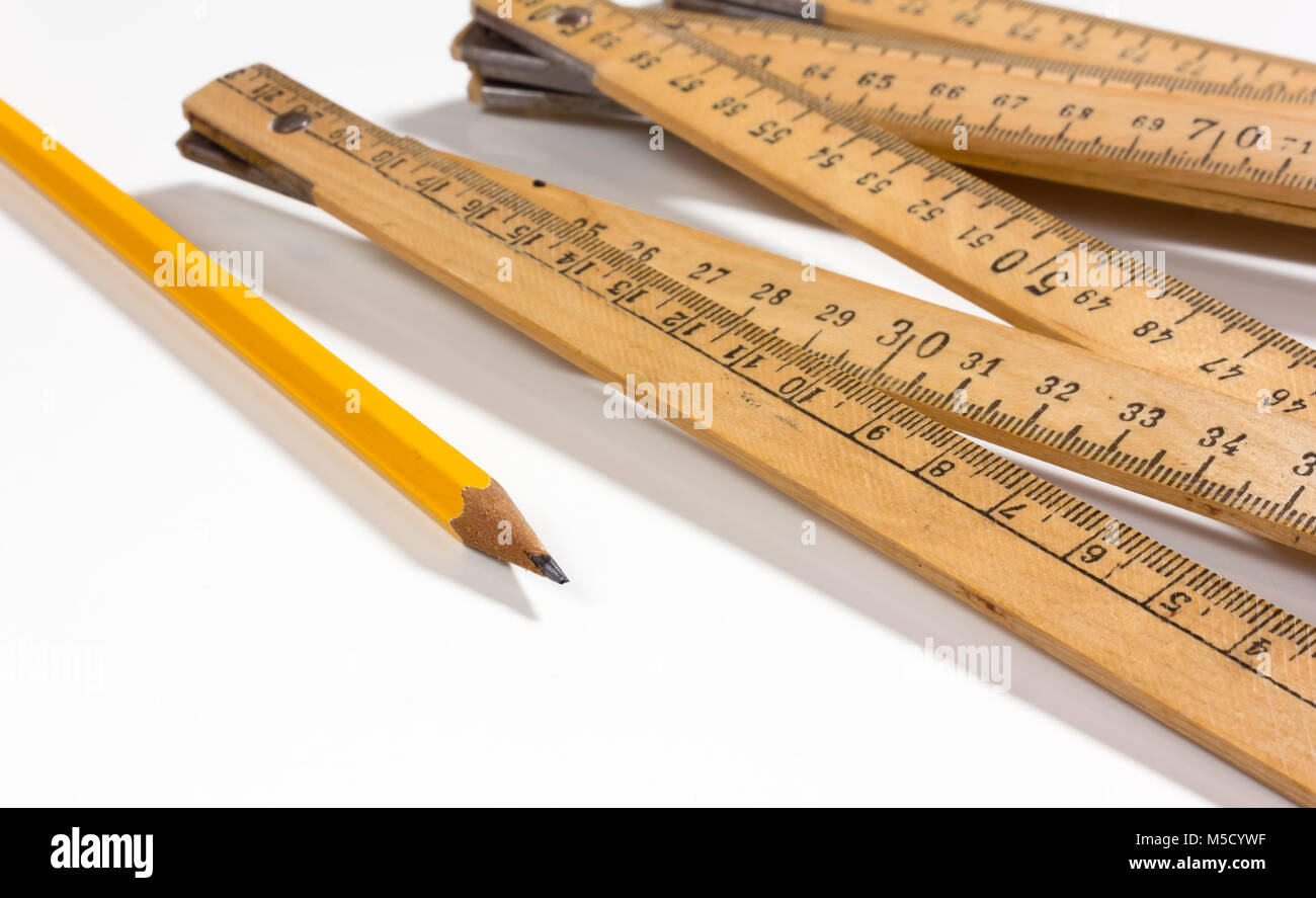 A measuring stick and a pencil on a white background - Stock Image