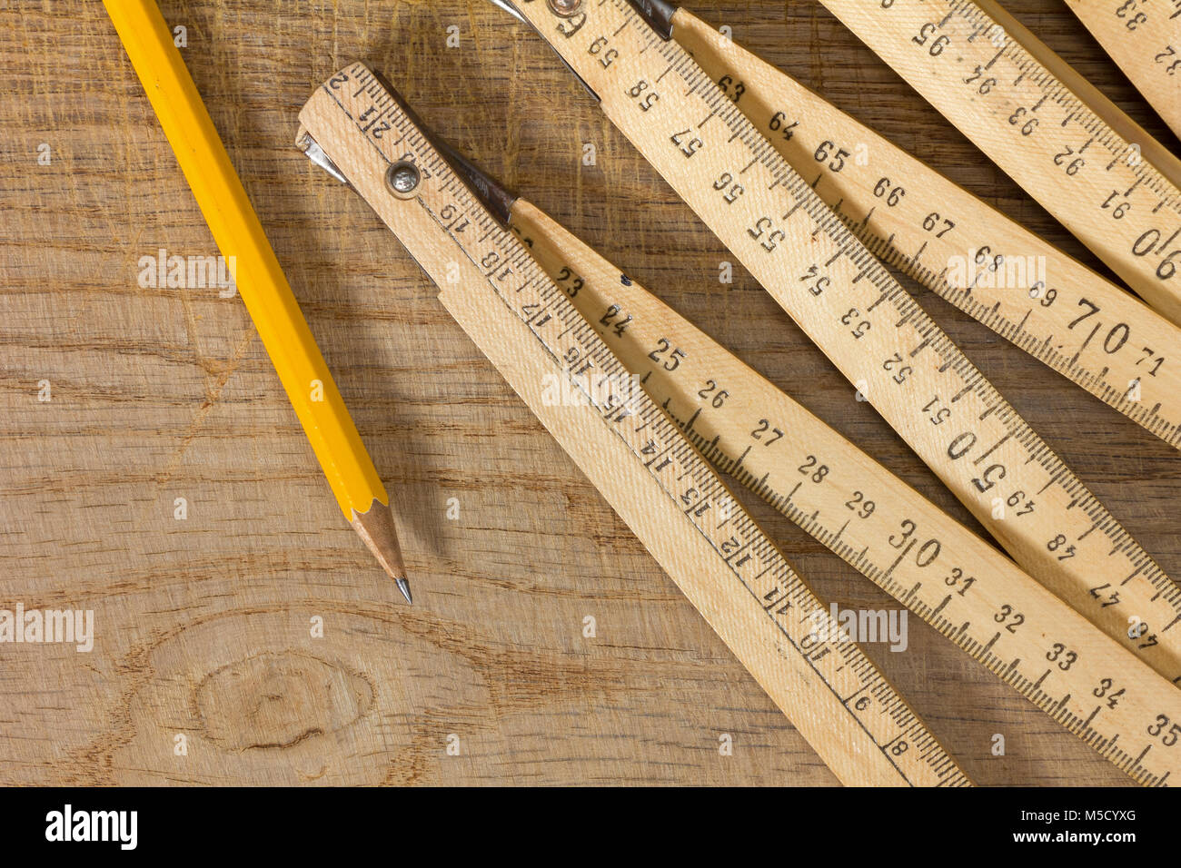 A measuring stick and a pencil on an old wooden table - Stock Image