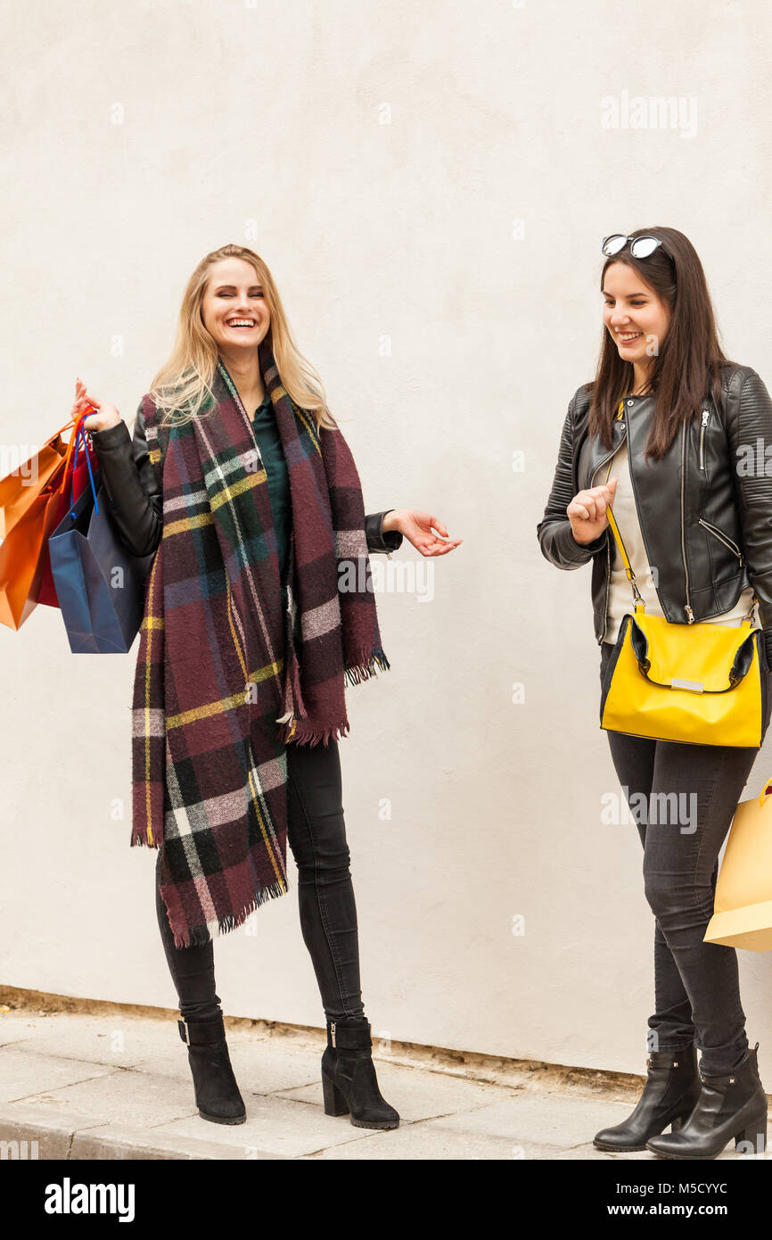 Happy girls laughing outside at cold weather. Spending money for gifts - Stock Image