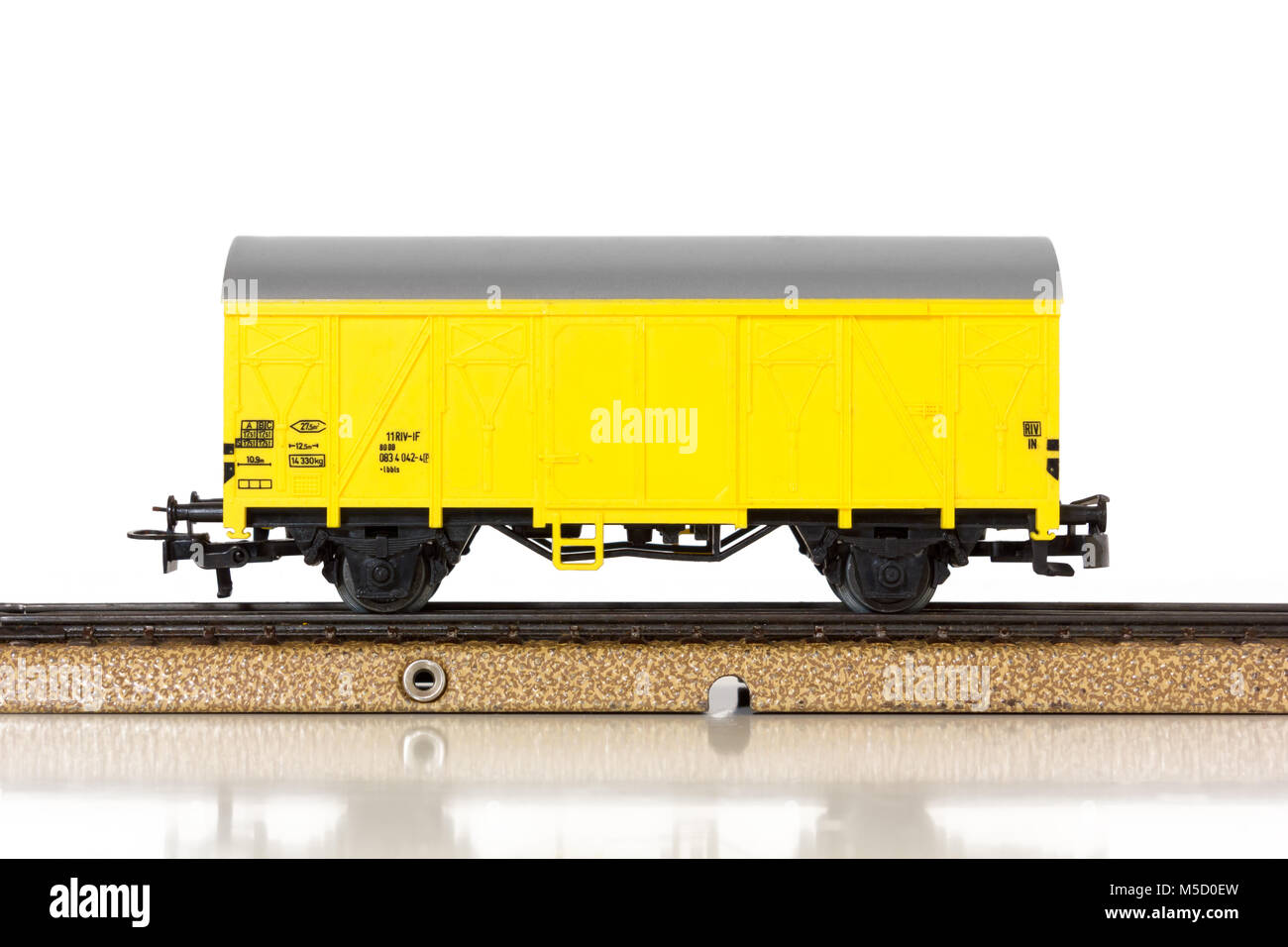 Yellow boxcar of an electric model train on the rails - Stock Image