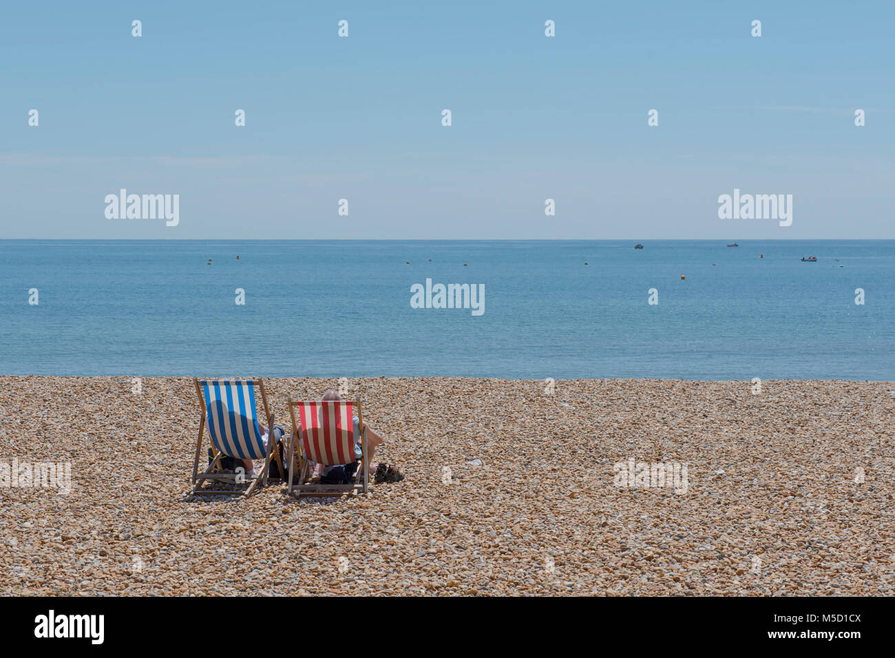 Soaring temperatures on the South Coast of England as Couple relax on traditional striped deckchairs with parasol - Stock Image