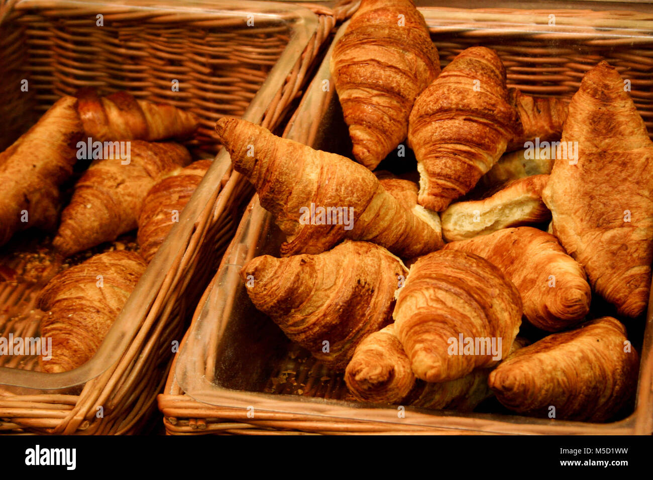 Puffy golden brown Croissants in sales wicker baskets, freshly baked, with natural lighting - Stock Image