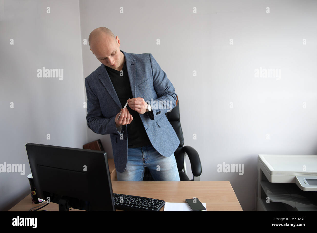 A young businessman working in a clean office with a computer and a cell phone, a portrait taken in the natural - Stock Image
