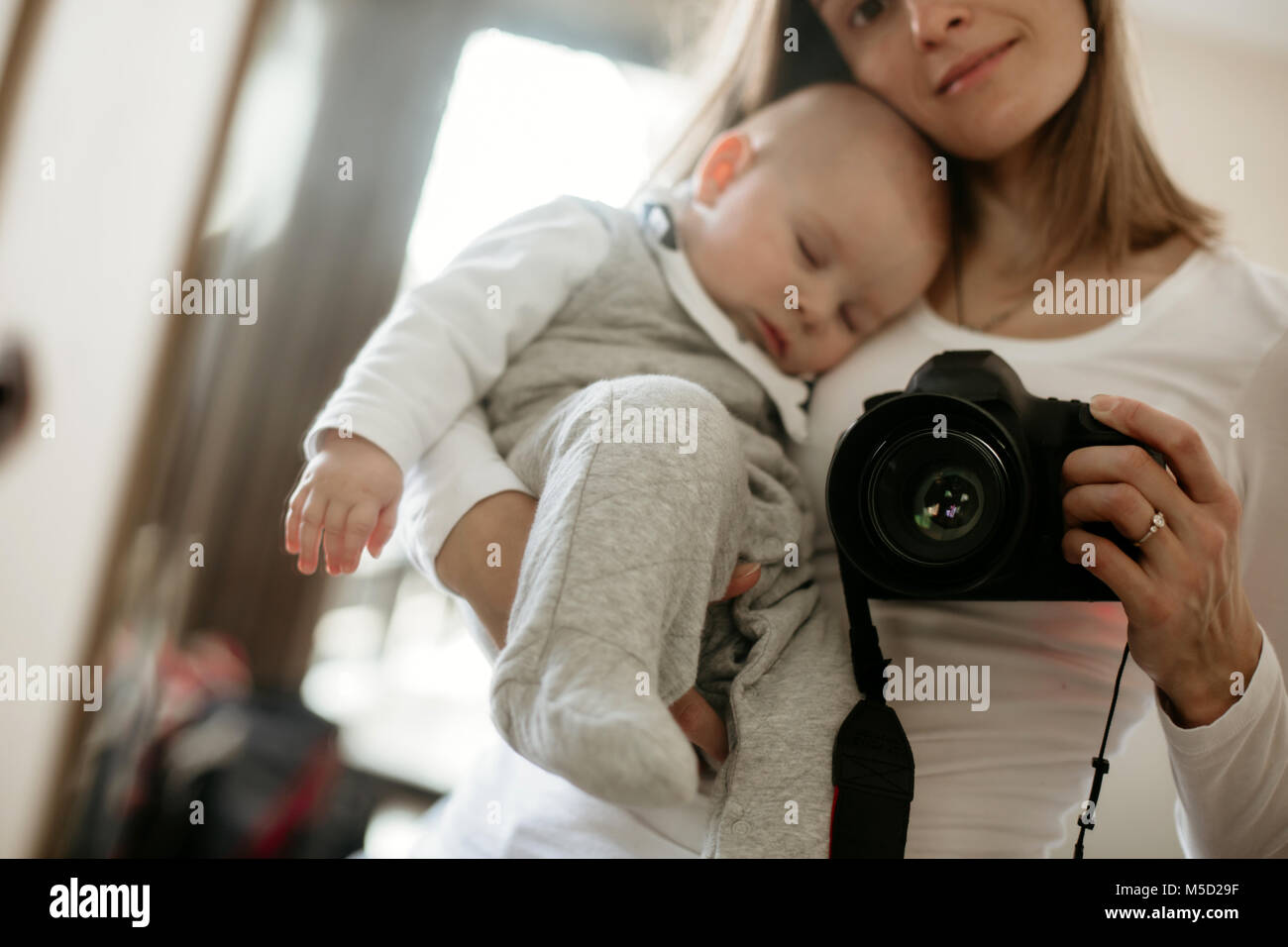 Young mother, holding tenderly her sleeping toddler boy, taking picture through a mirror, sunny living room - Stock Image