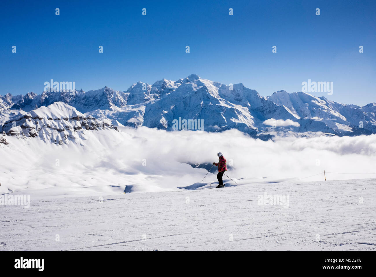 One skier skiing on snow ski slope with Mont Blanc as backdrop in French Alps. Tetes des Lindars, Flaine, Haute - Stock Image
