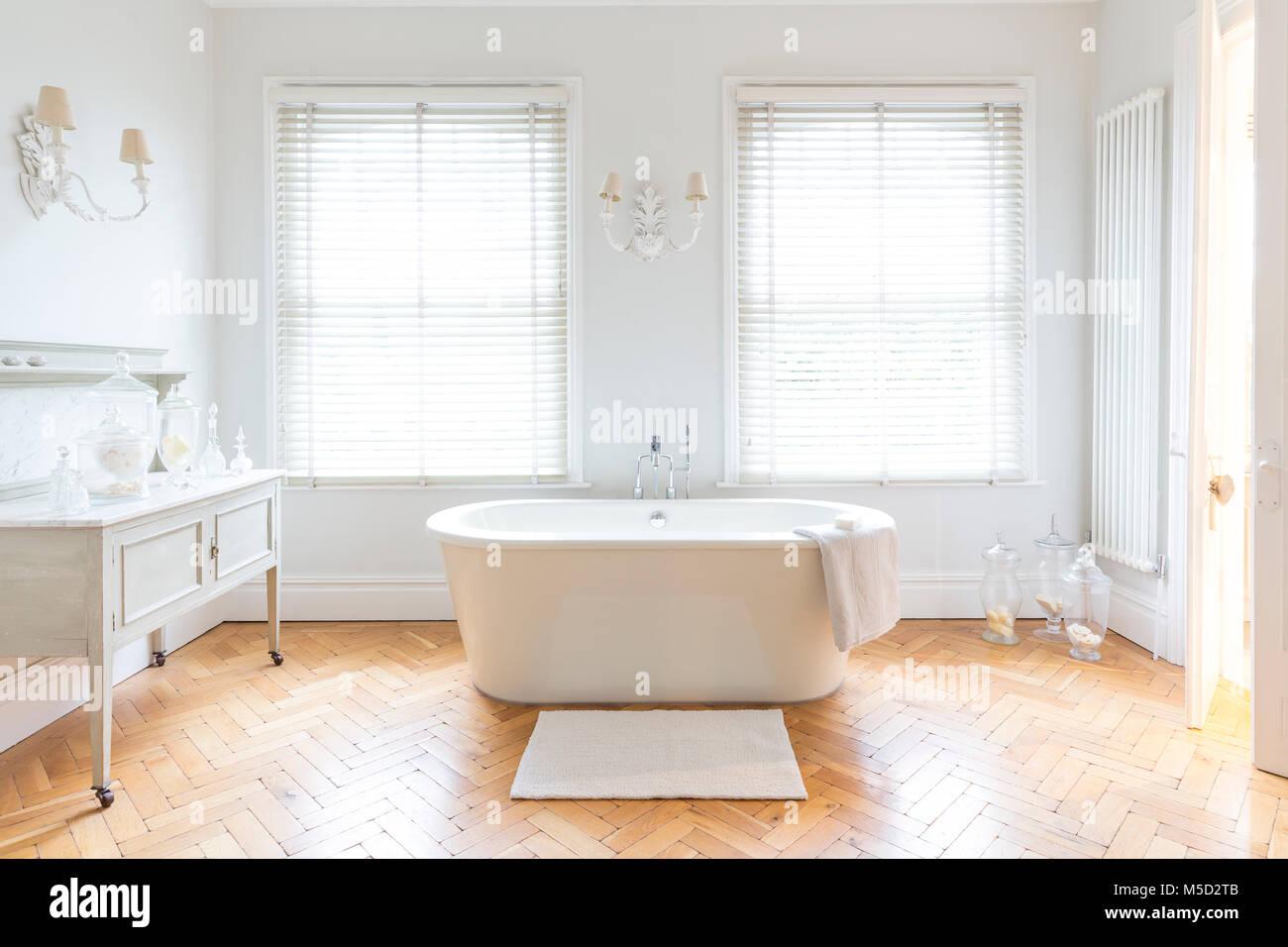 White, luxury home showcase bathroom with soaking tub and parquet ...
