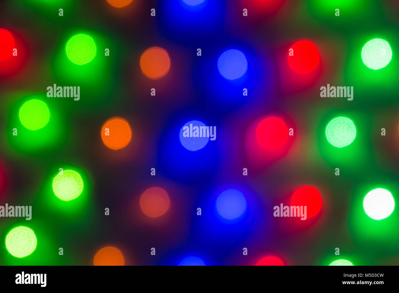 Abstract image of defocused varicolored round lights in a row closeup - Stock Image