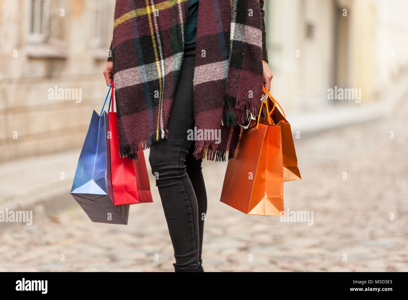 Woman holds bags in a cold day - Stock Image
