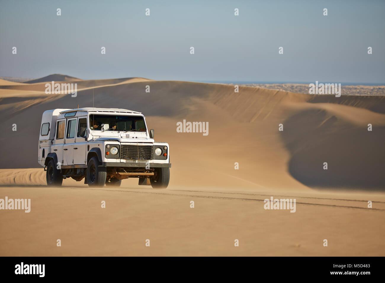 Off-road vehicle drives over sand dunes at Lange Wand on the Atlantic coast, Namib-Naukluft-Park, Namibia - Stock Image