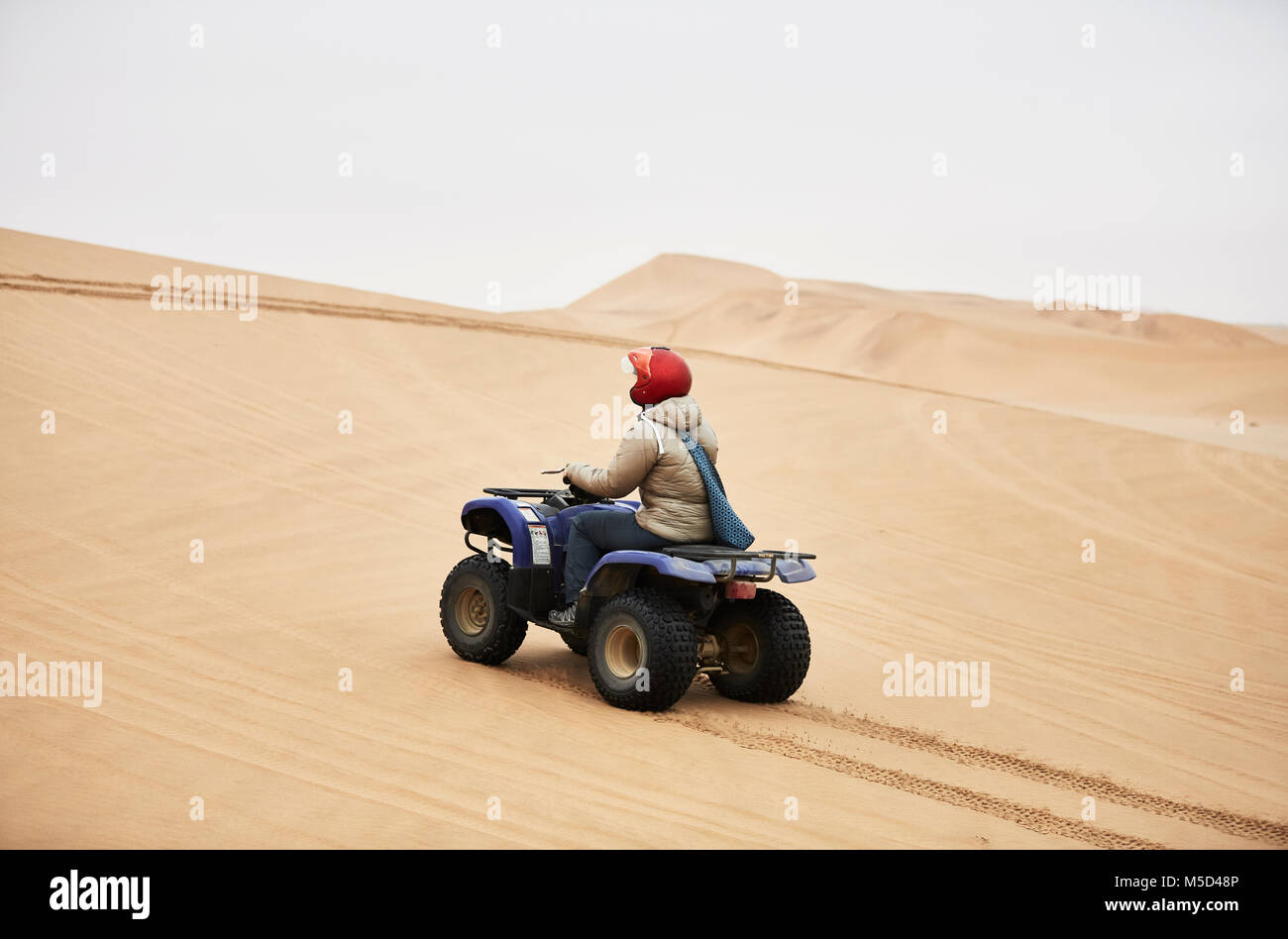 Woman drives with Quad over sand dunes at Swakopmund, Namibia - Stock Image