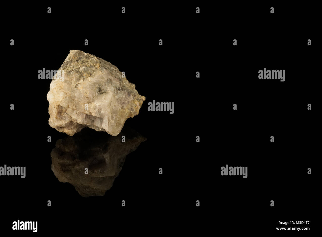 Cassiterite, tin oxide mineral, tin ore isolated on black background. Ditetragonal dipyramidal crystal structure. - Stock Image