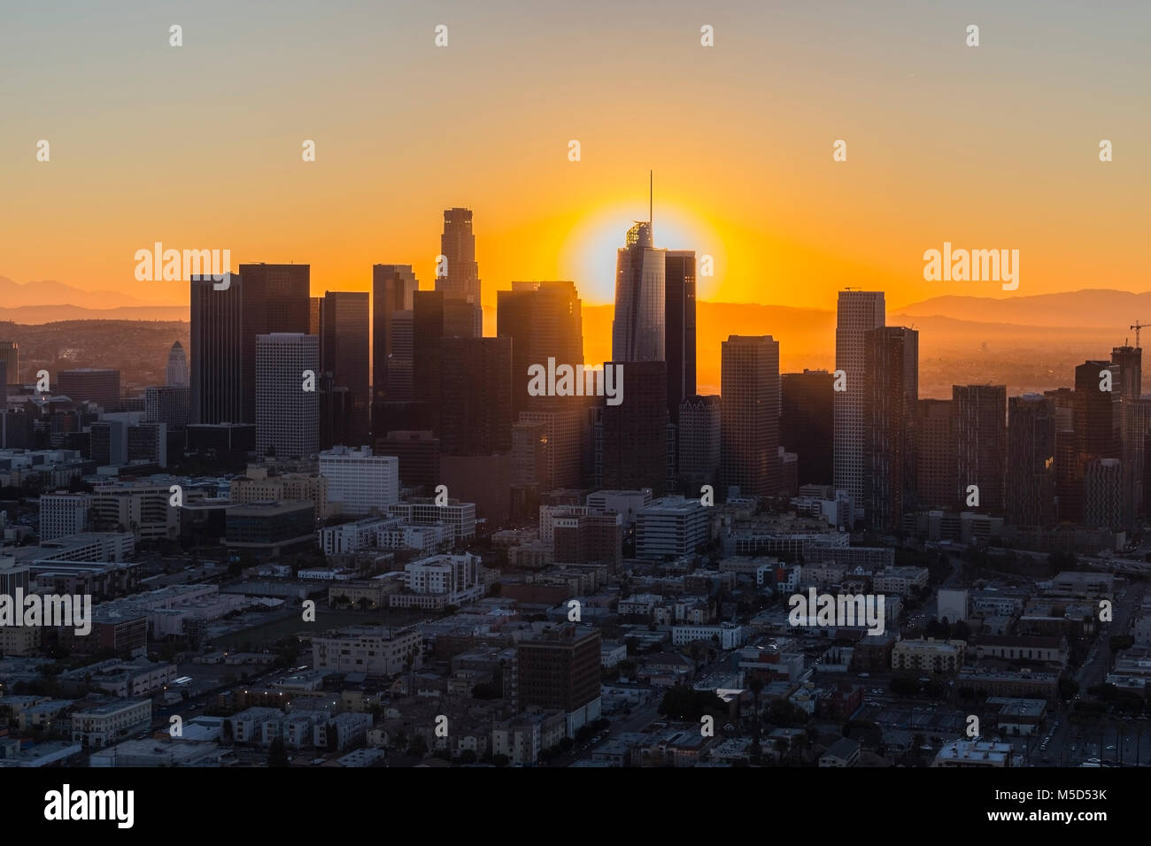 Dawn aerial view of rising sun behind downtown Los Angeles in Southern California. Stock Photo