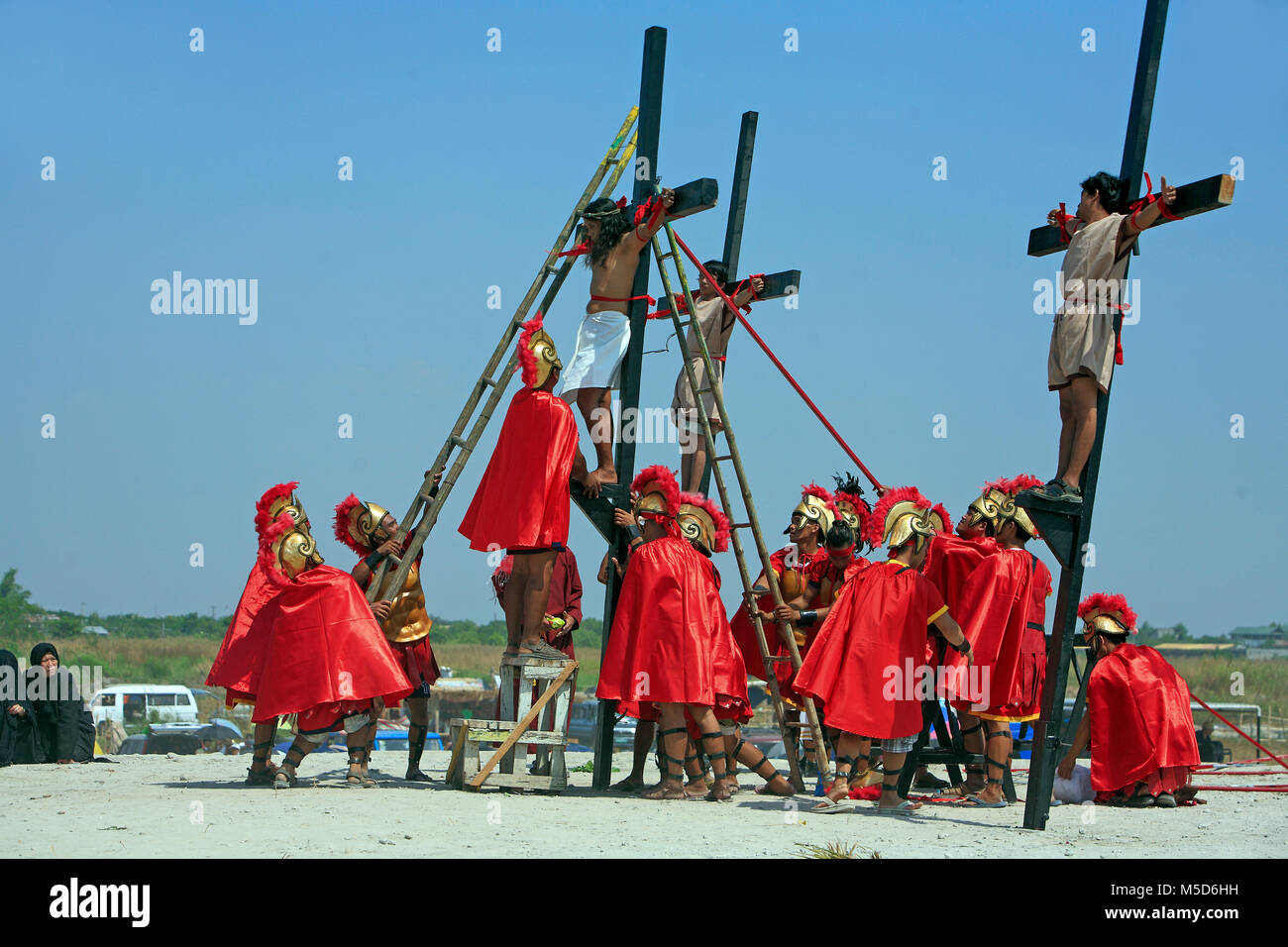 Crucifixion, Roman soldiers crucify Filipinos, religious ritual on Good Friday, public self-flagellation of the - Stock Image