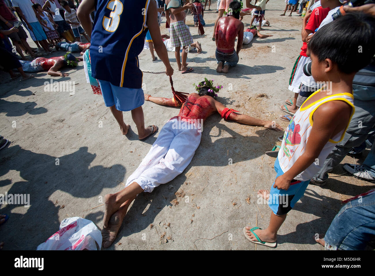 Filipino beats a flagellant exhausted on the ground, religious ritual on Good Friday, public self-flagellation of - Stock Image