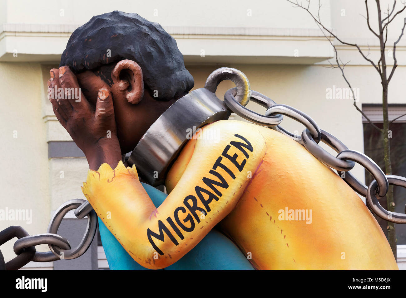 Migrant from Africa, double chained, slavery sponsored by the EU, political caricature, motto caravan during Carnival - Stock Image