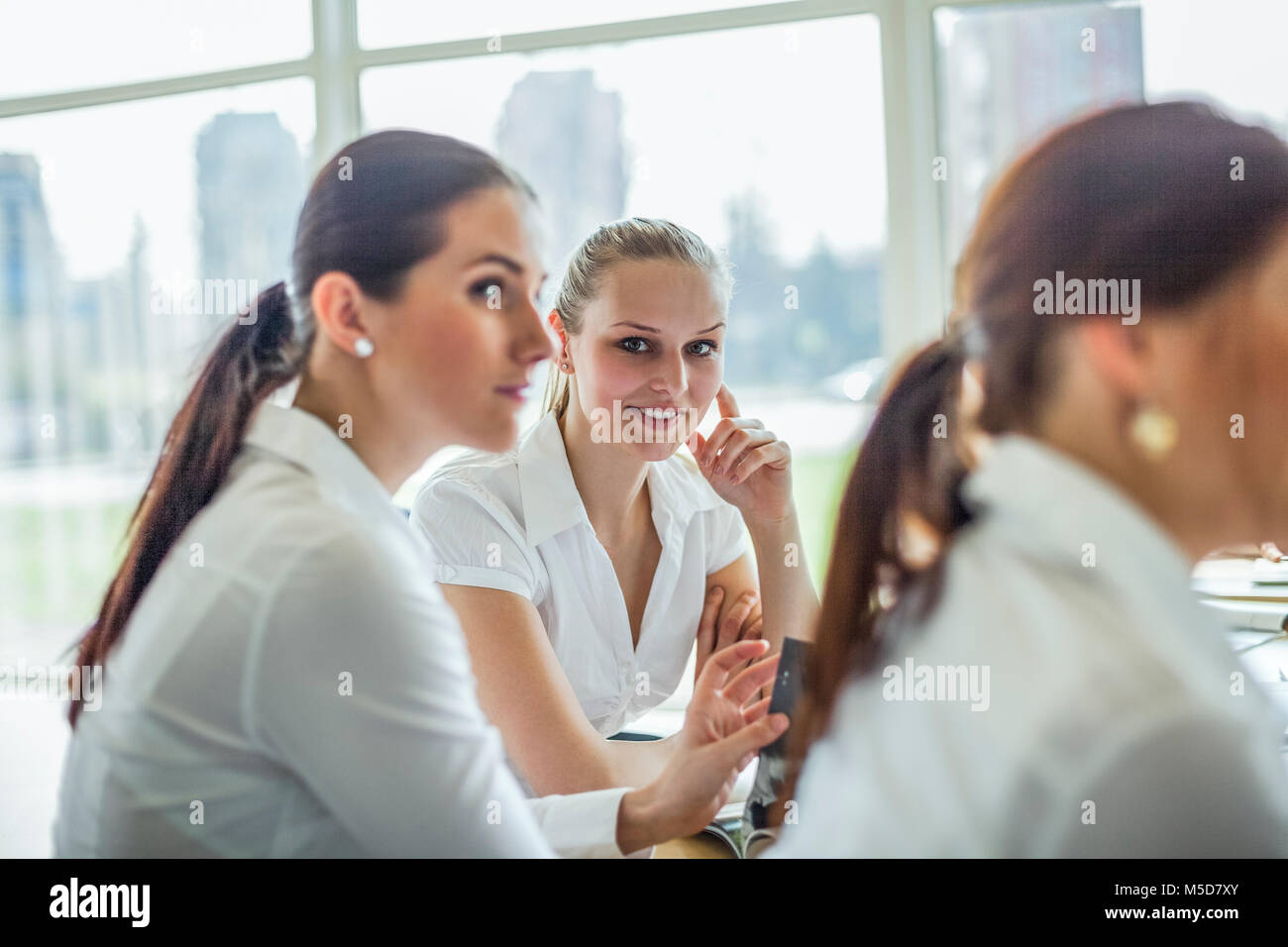 Portrait of beautiful young businesswoman with female colleagues in board room - Stock Image