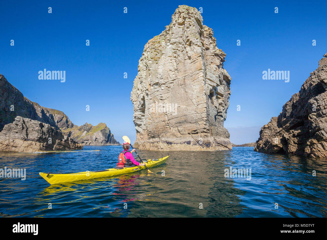 Sea kayaking past a massive stack near Port, Glencolmcille, County Donegal, Ireland. - Stock Image