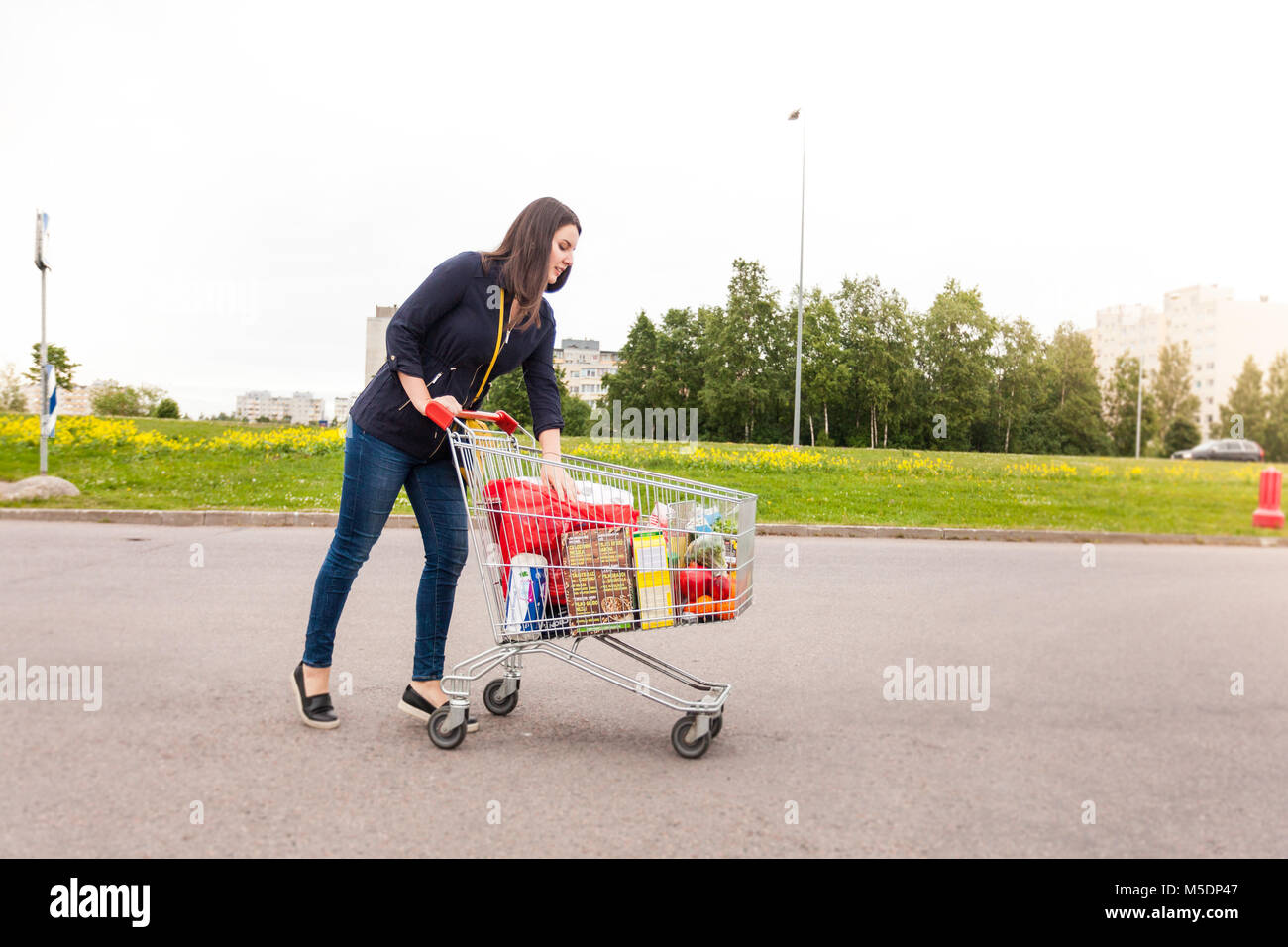 Slim girl is happy with product she bought in a store - Stock Image