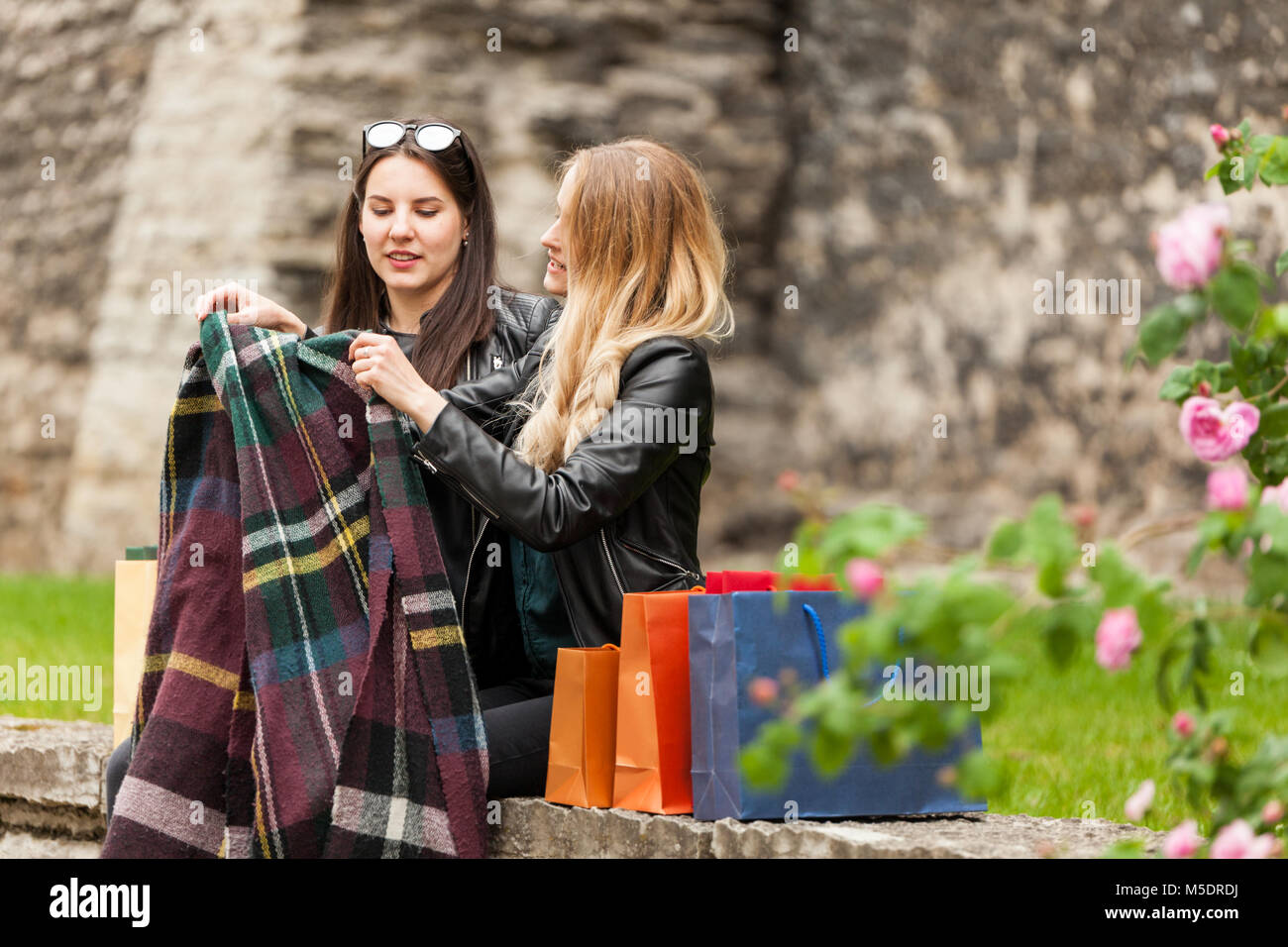 Two cute girls cover with a blanket in a cold day - Stock Image