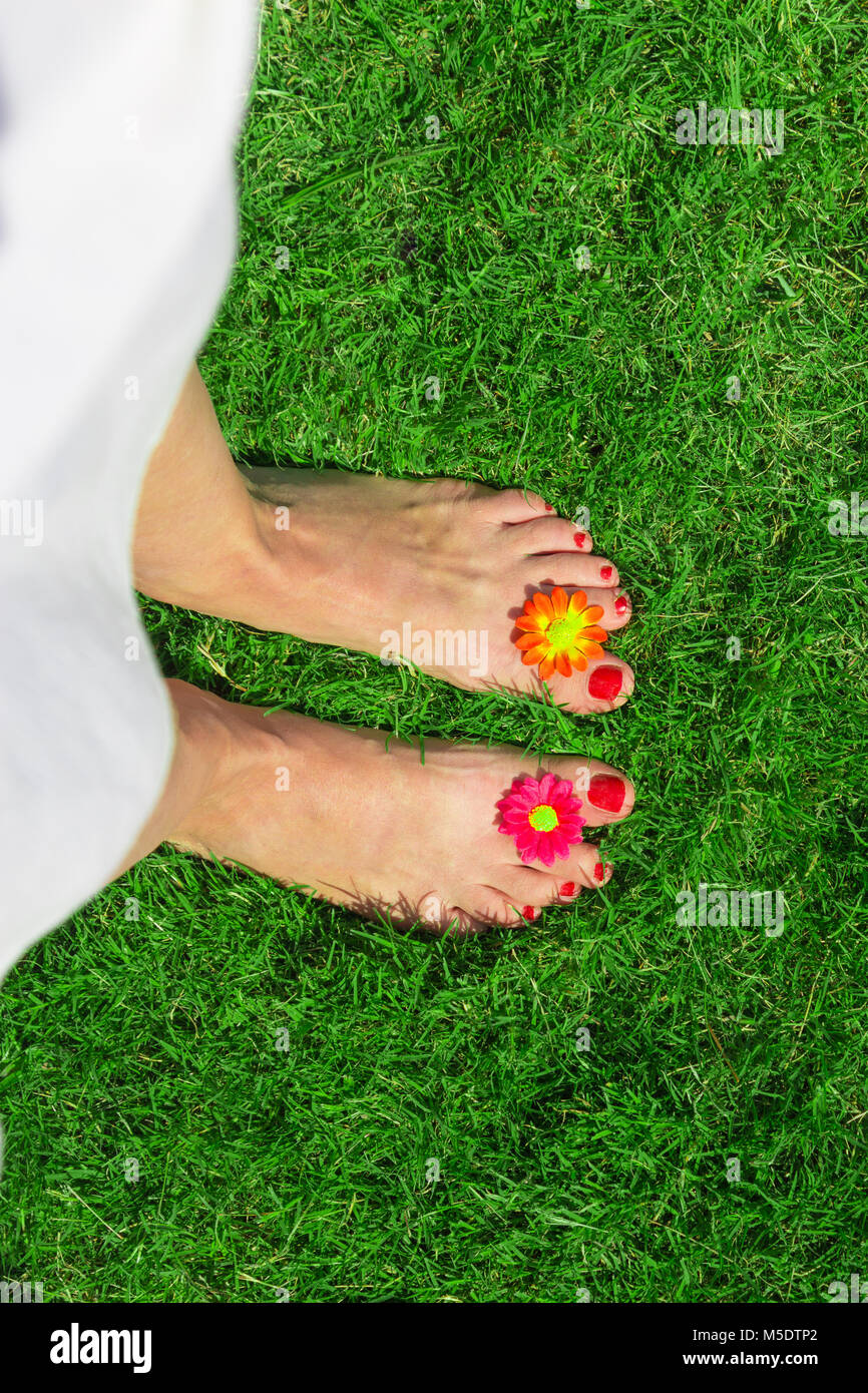 Top-down perspective of female feet decorated with flowers on green grass - Stock Image