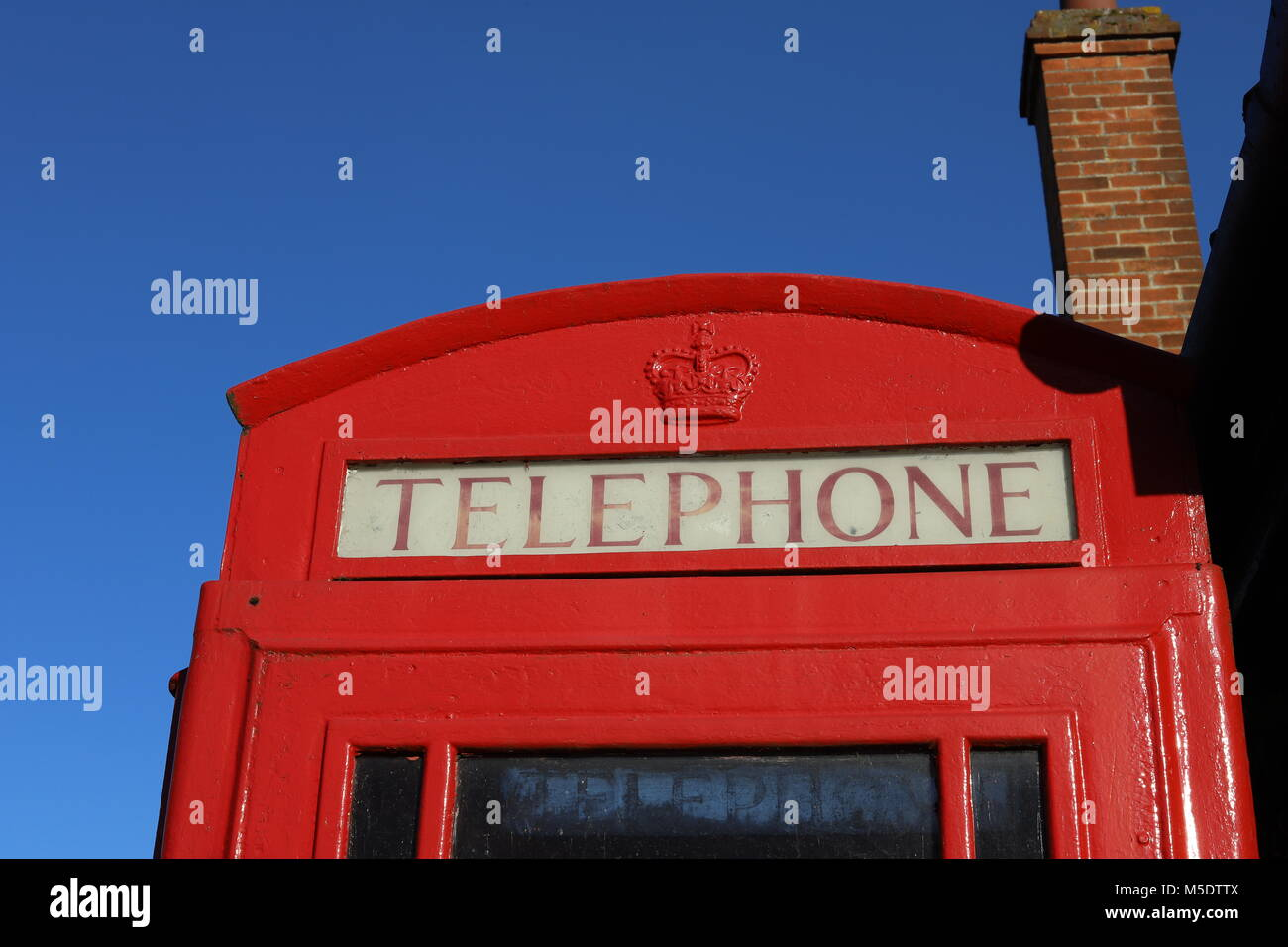 Old red post office / BT telephone box outside The Maybush pub in Waldringfield, Suffolk. - Stock Image