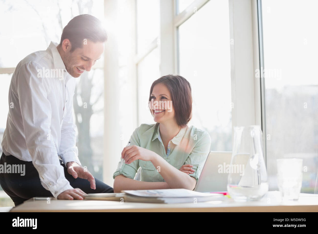 Happy young business people discussing at desk in office - Stock Image