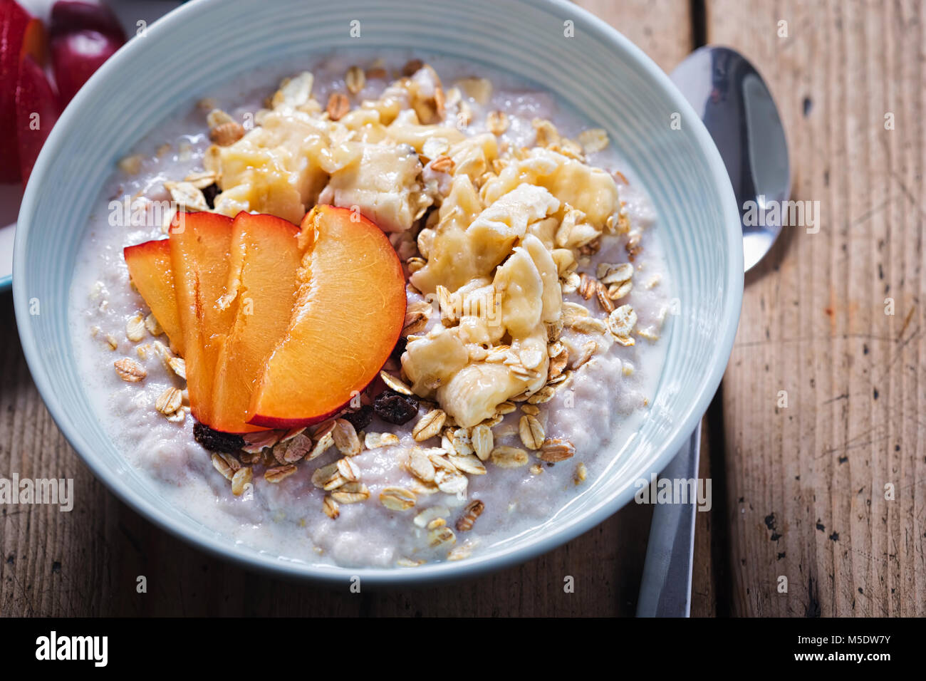 Strawberry porridge with oats, mashed banana and plum - Stock Image