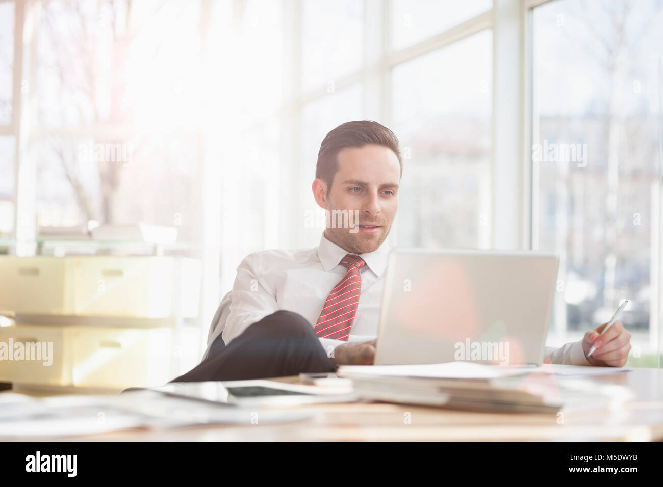 Young businessman using laptop at office desk - Stock Image