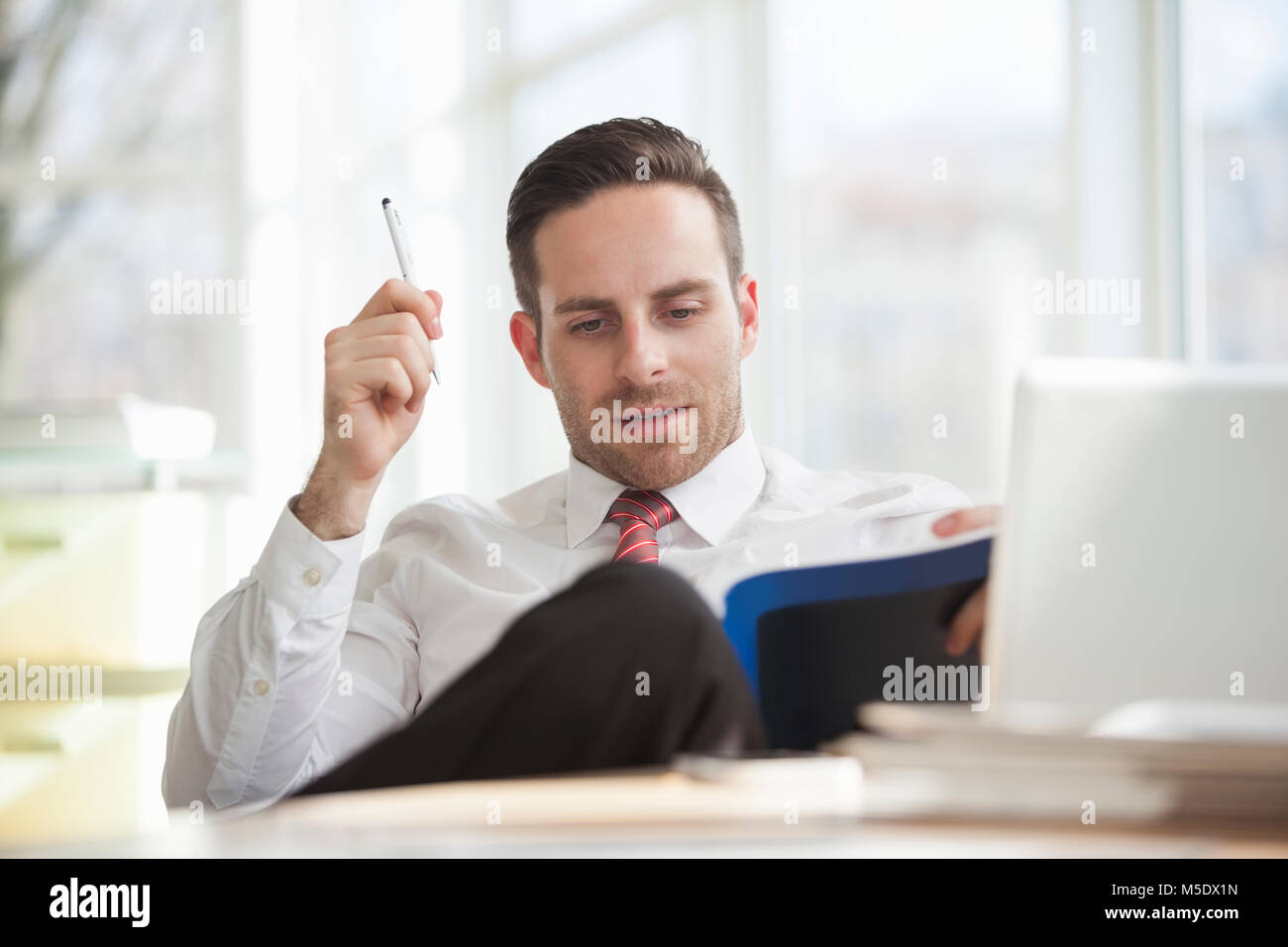 Young businessman reading book in office - Stock Image