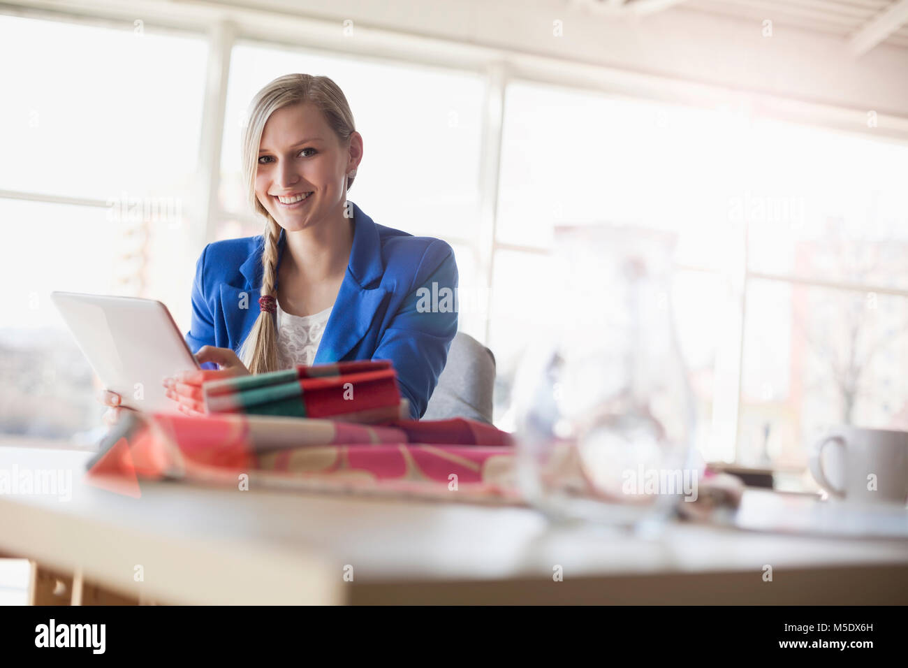 Portrait of confident young businesswoman using digital tablet at desk in creative office - Stock Image