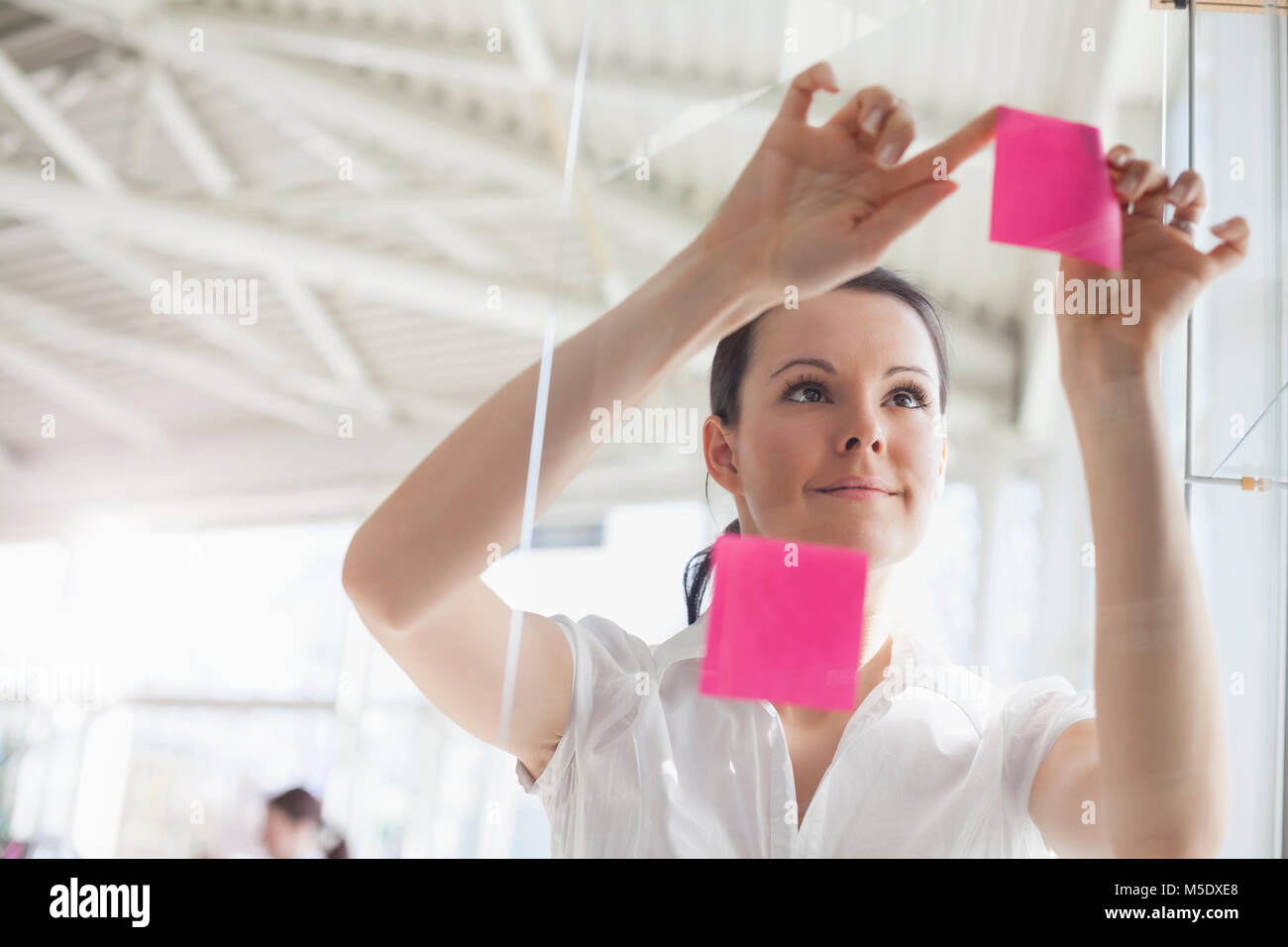 Beautiful young businesswoman putting sticky notes on glass wall in office - Stock Image
