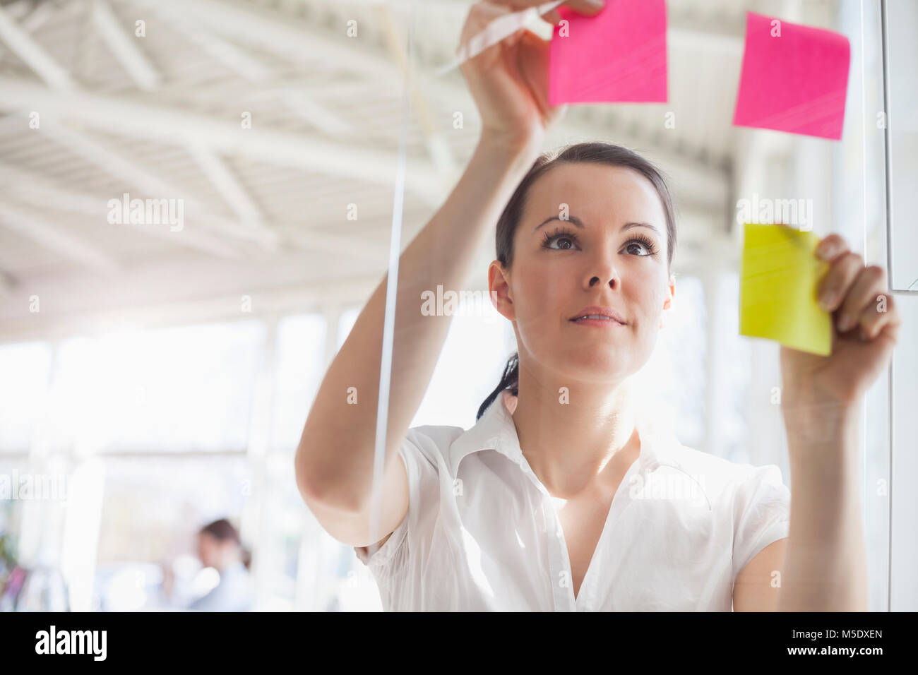 Beautiful young businesswoman putting adhesive notes on glass wall in office - Stock Image