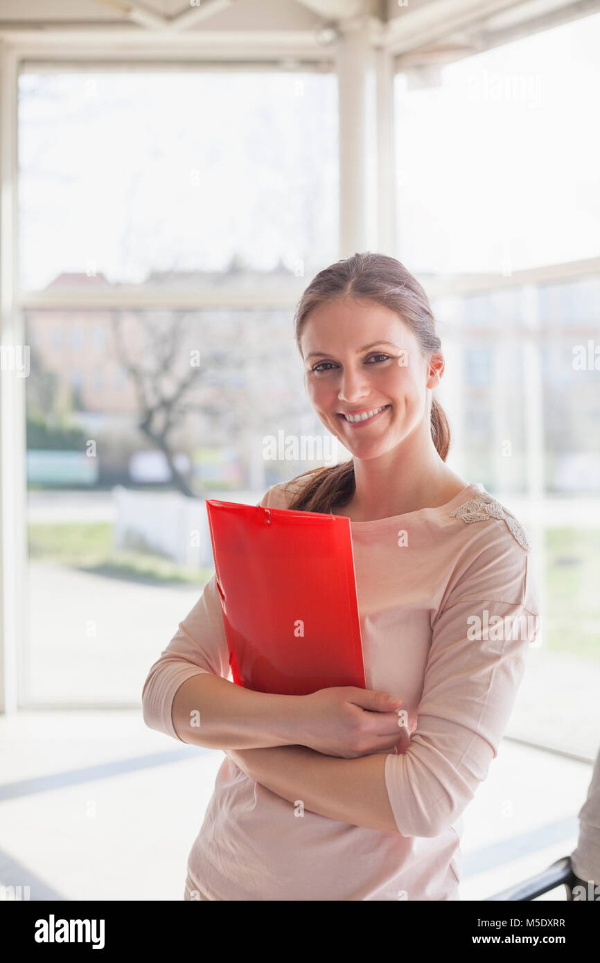Portrait of beautiful young businesswoman holding folder in office - Stock Image