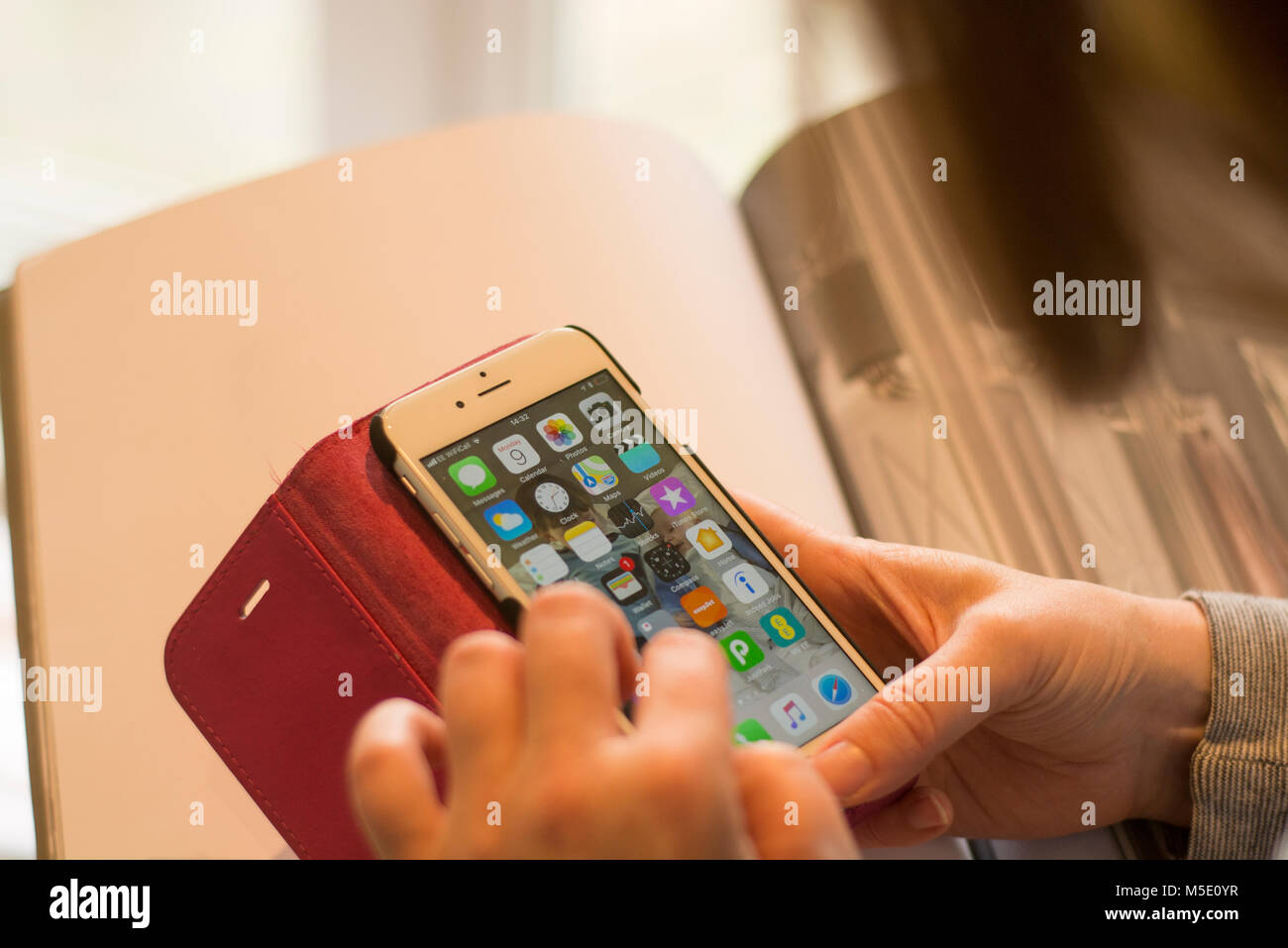 A woman using her iPhone, with a number of apps on the home screen - Stock Image