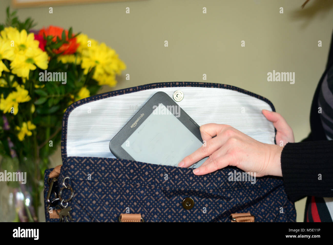 Woman taking a Kindle e-reader out of her handbag - Stock Image