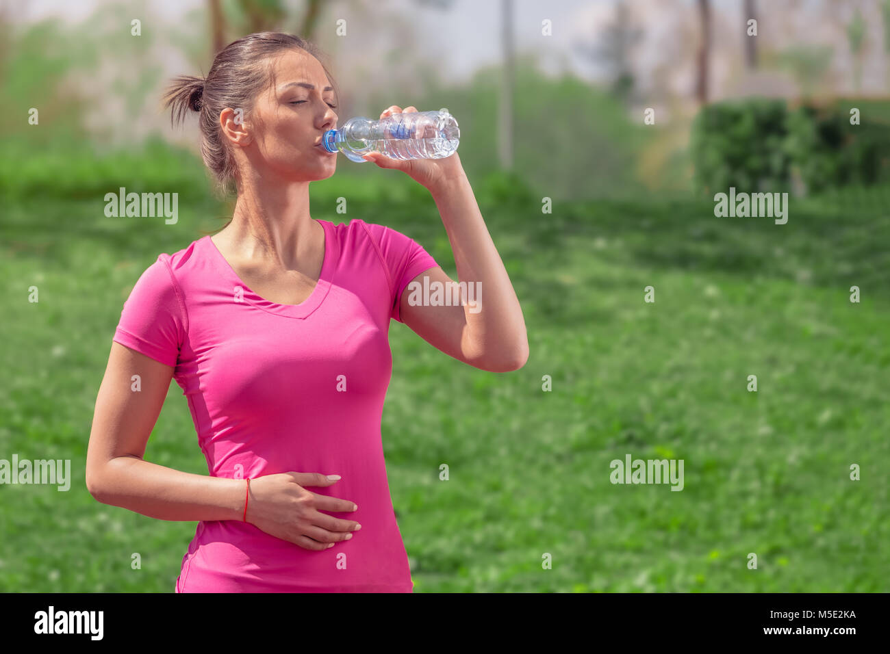 Fitness runner woman drinking water in the park. Athlete girl taking a break during run to hydrate during hot summer - Stock Image
