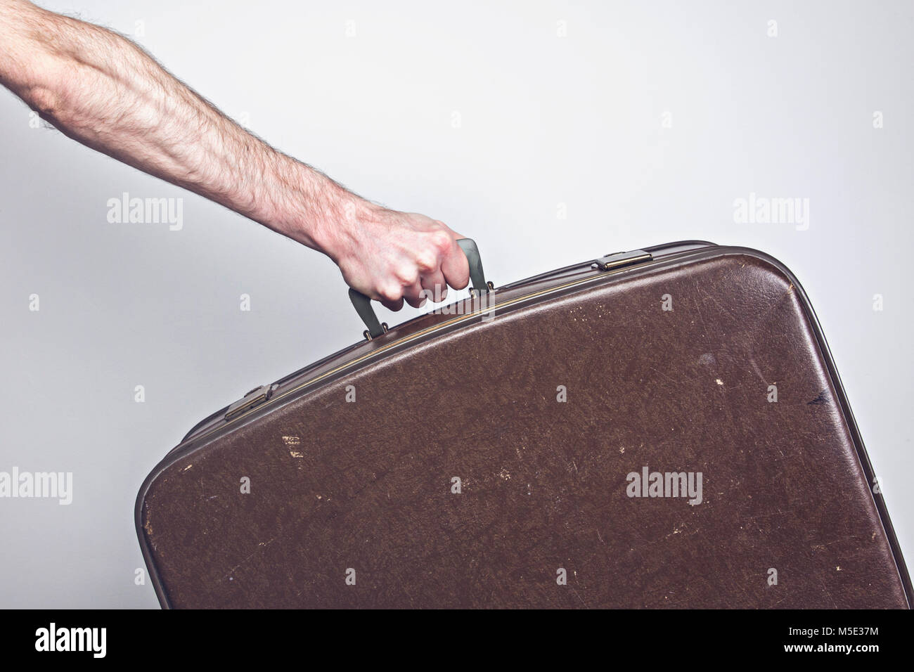 Travel concept. Person holding a vintage travel suitcase - Stock Image