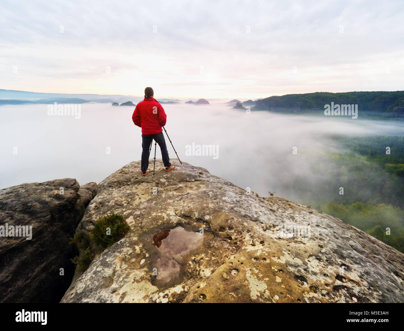 Professional photographer and hiker shooting in wild nature with a digital camera and a tripod. View over clouds - Stock Image