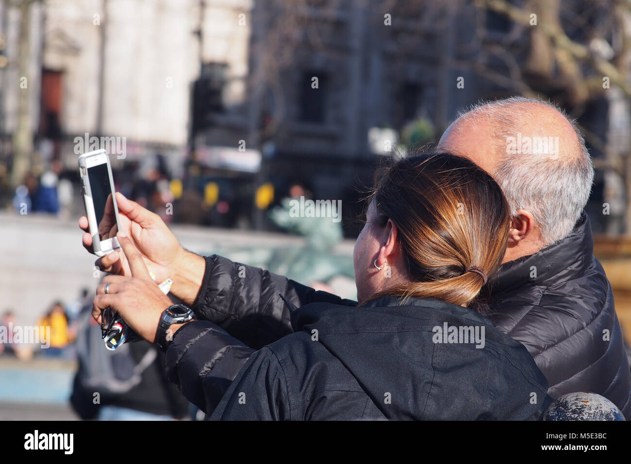 Man and woman composing a selfie on a smartphone in Trafalgar Square, London - Stock Image