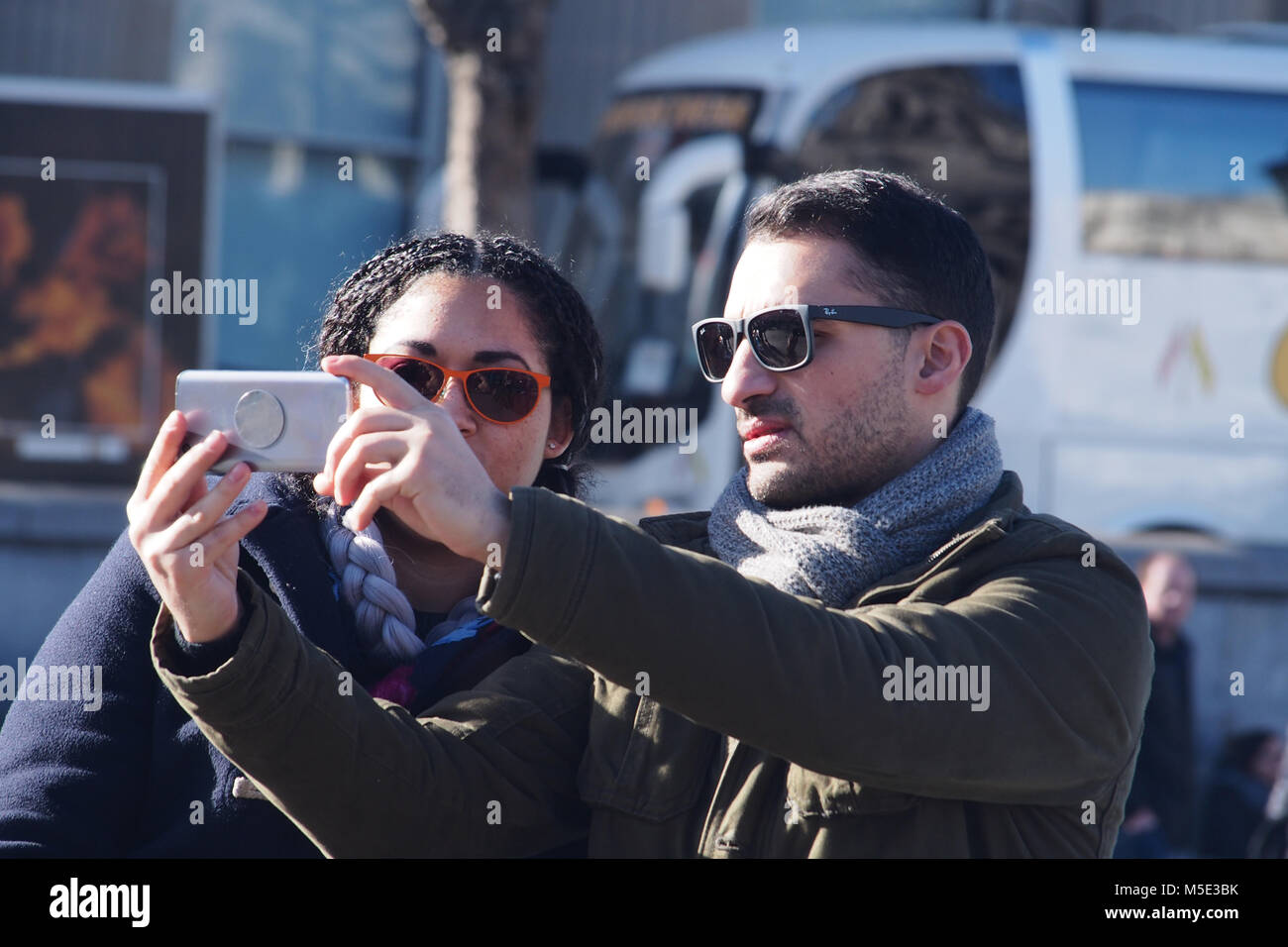 A young couple taking a selfie with a smartphone wearing sunglasses in the winter sunshine in Trafalgar Square, - Stock Image