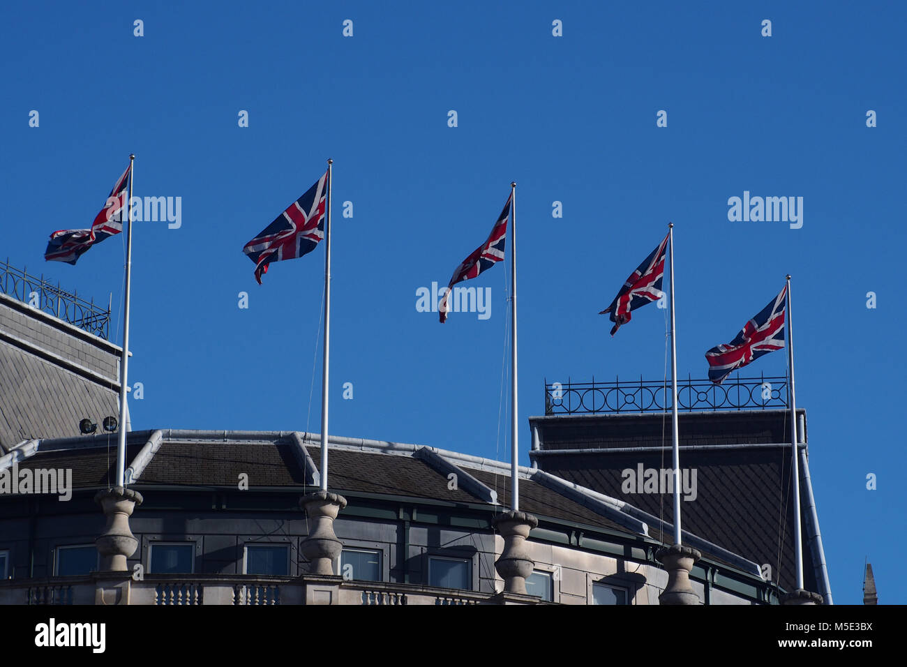 A row of Union flags flying on top of a building next to Trafalgar Square, London against a blue sky - Stock Image