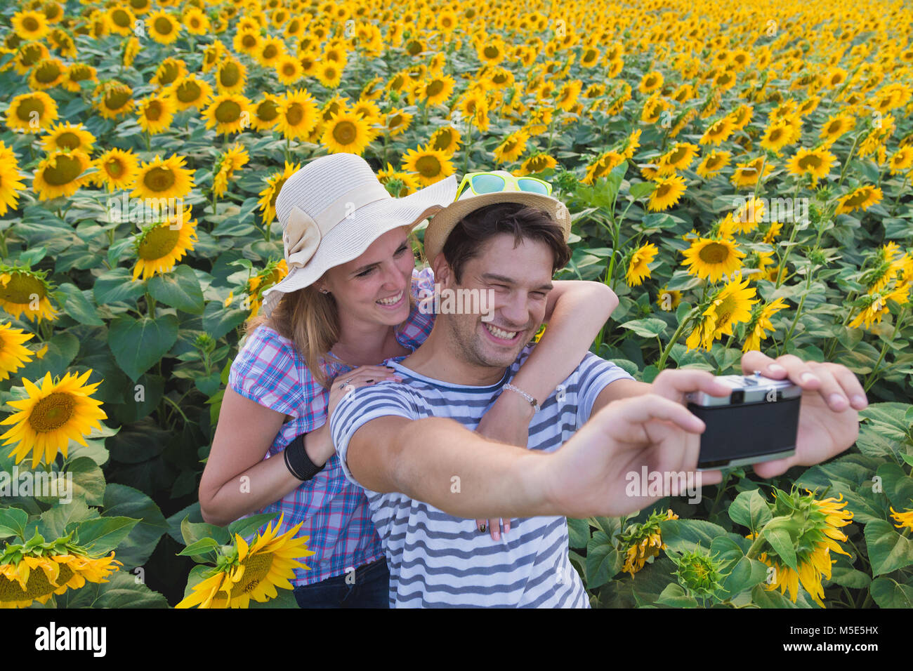 Young heterosexual couple taking selfie in sunflower field by using retro vintage film camera. Love and summertime Stock Photo