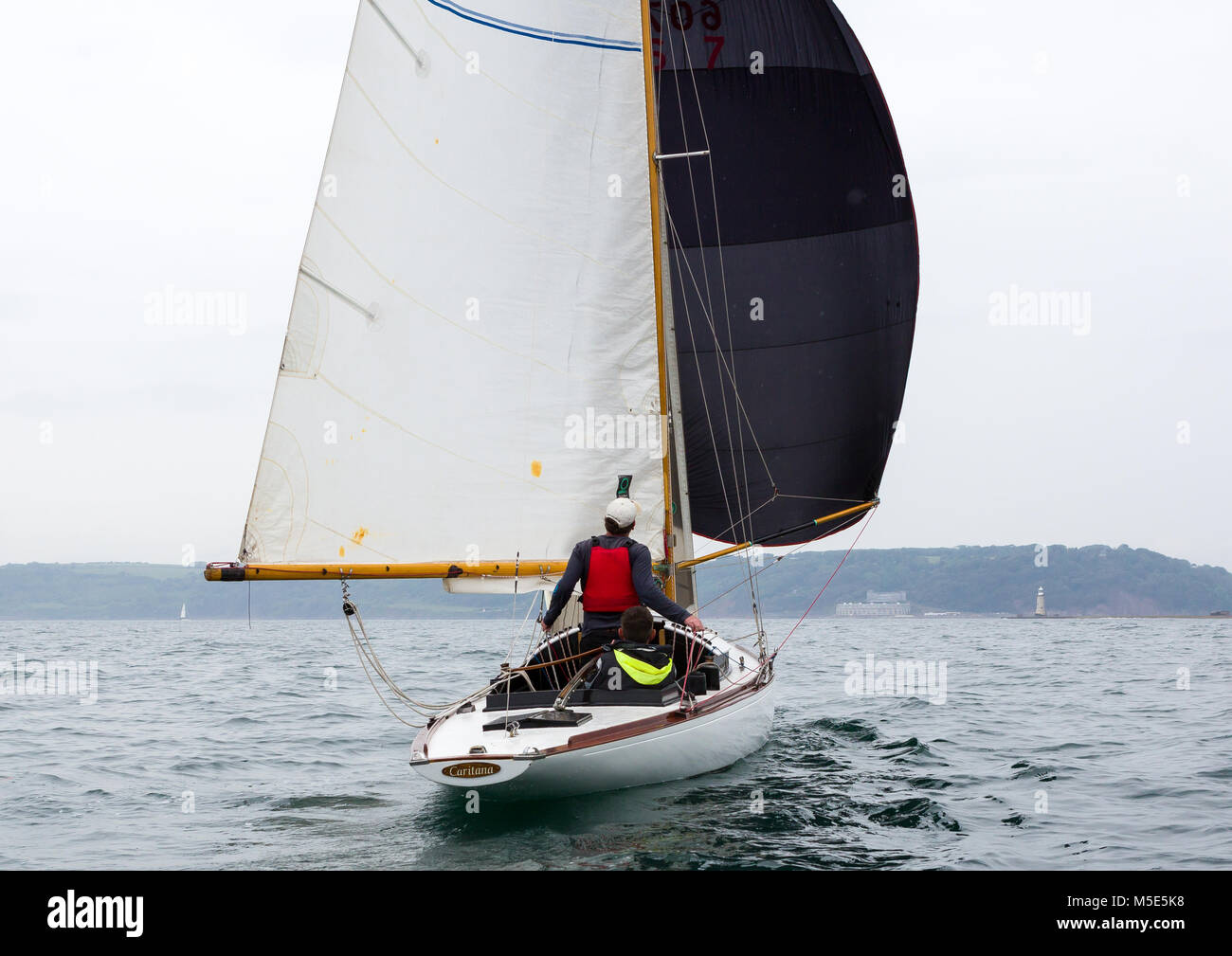 A crew member on the yacht Caritana trims the spinnaker during a classic boat race in Plymouth Sound - Stock Image