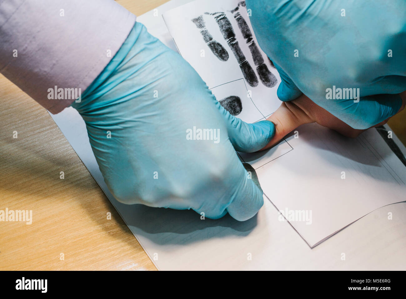 The investigator takes fingerprints from the suspect in the crime. Investigation is a crime. Crime. - Stock Image